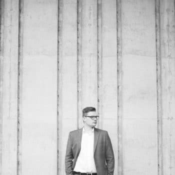 Joshua Wyborn of Joshua wyborn photographic standing in front of a wall out side a Lake District Wedding Venue
