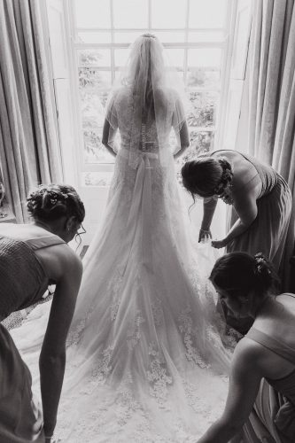 Bride looking out of window as bridesmaids fix her dress in long marton cumbria lake district wedding photographer