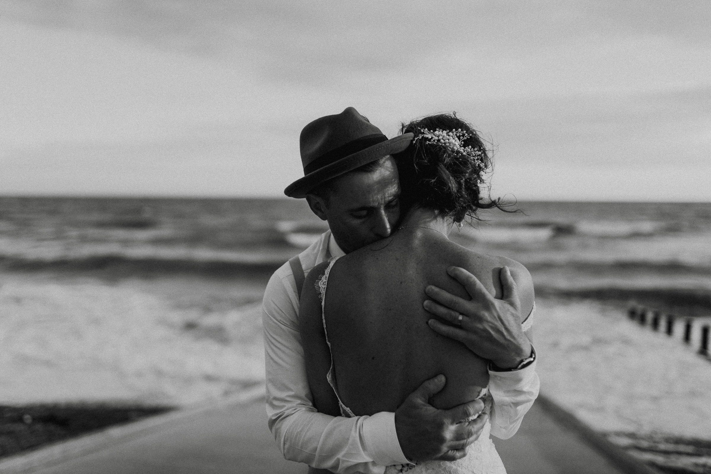 Groom embracing Bride at St Bees Beach Cumbria by featured Lake district and Cumbria wedding photographer Joshua Wyborn