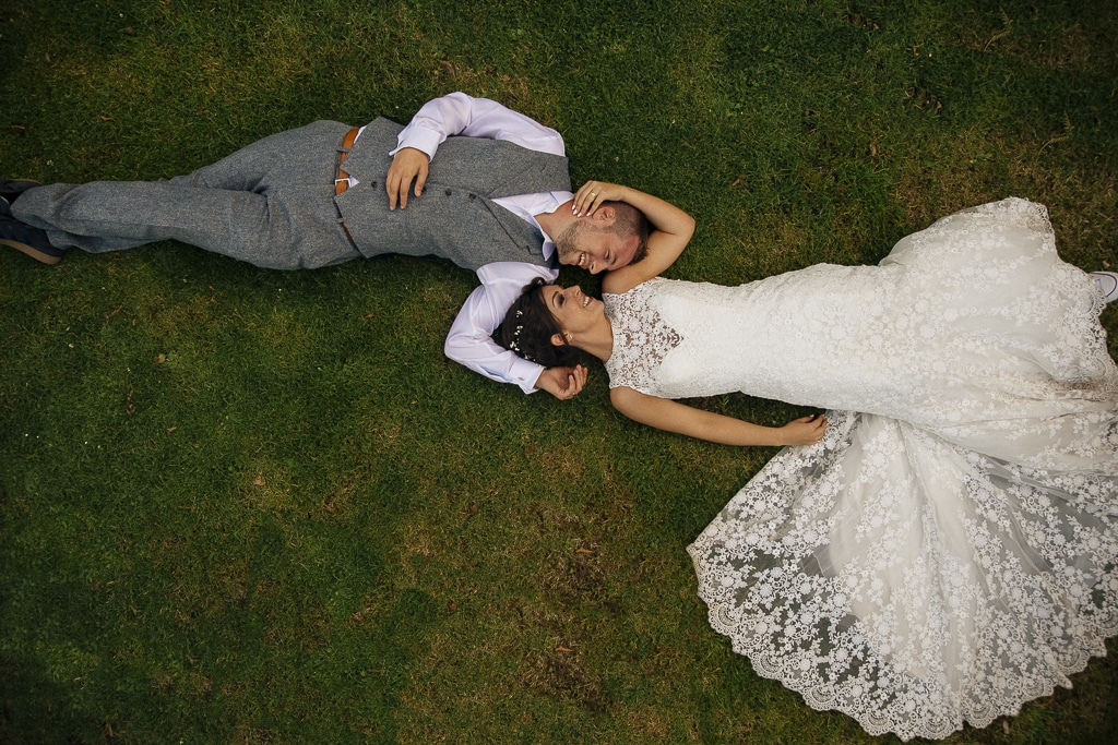 Wedding Couple laying down on the grass in a creative wedding photograph by Joshua Wyborn at a Lake district wedding.