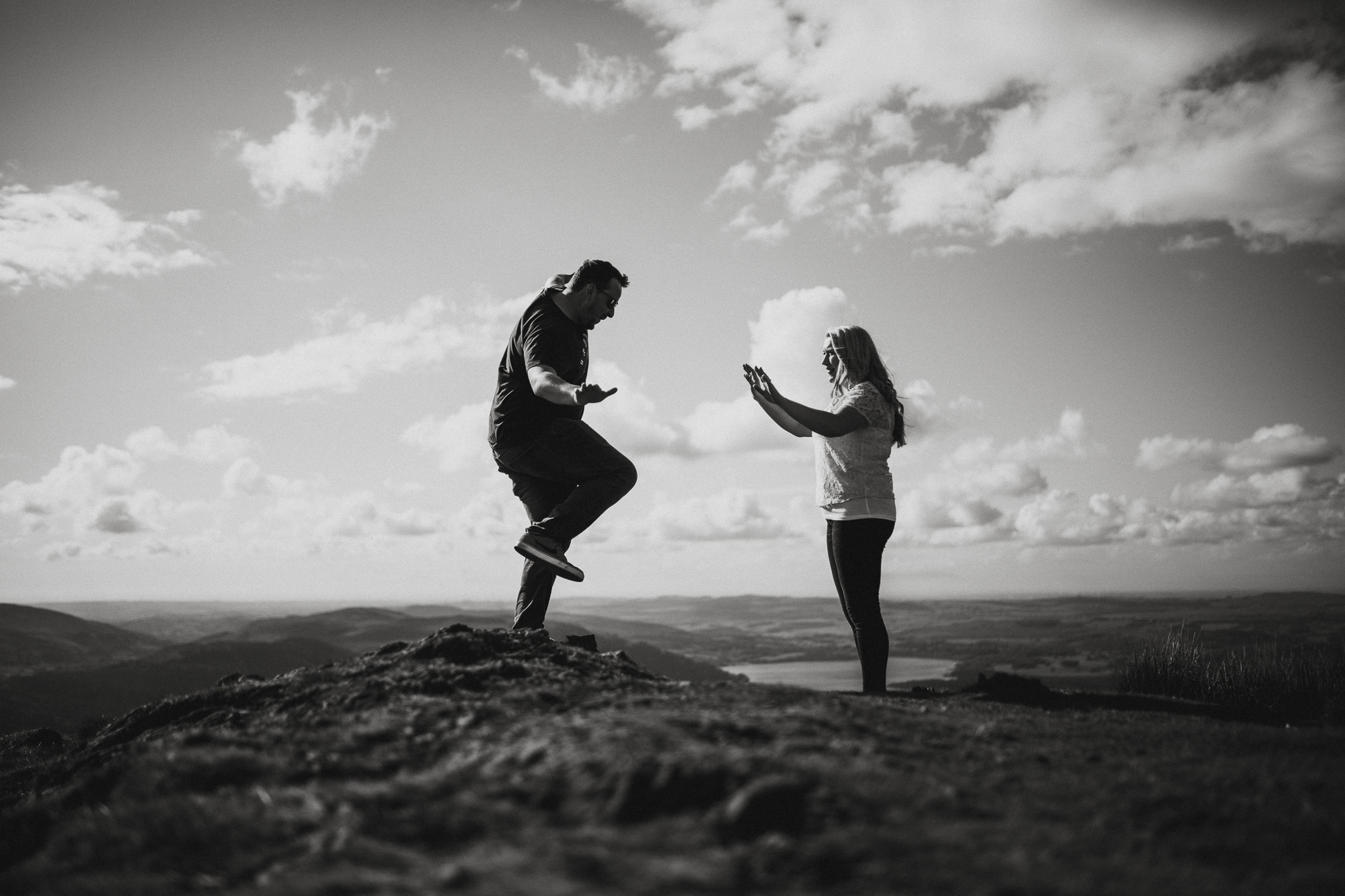 couple playing on fellside above lakes int he lake district
