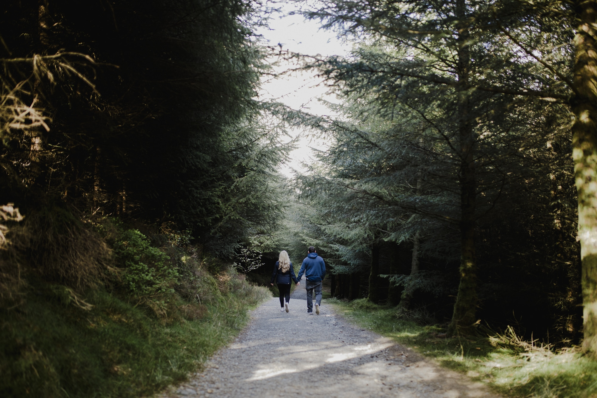couple walking down a path in dodds wood in the lake district