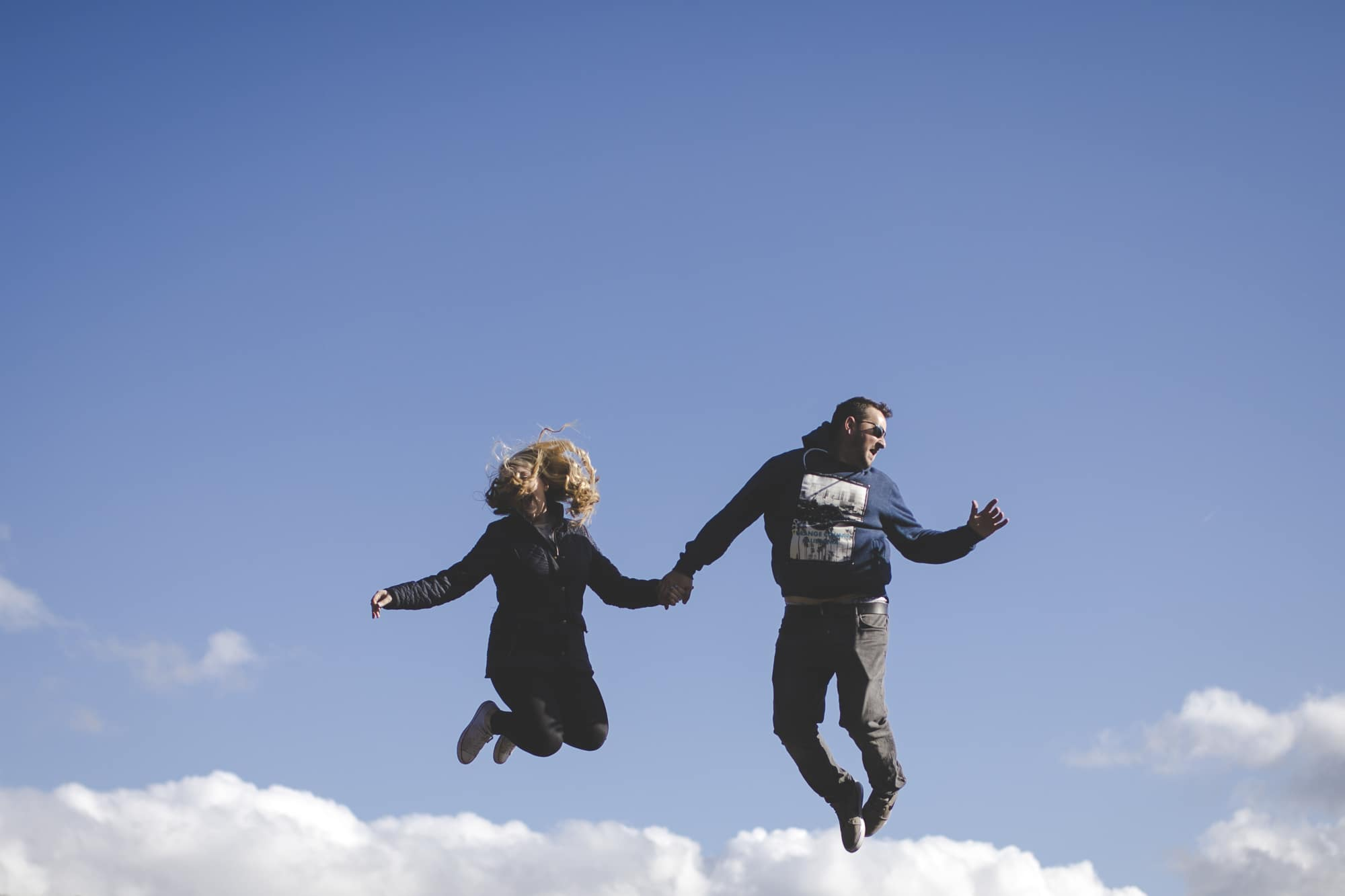 Couple jumping high in the air on a lake district fell top. Lake District & Cumbria Wedding Photographer