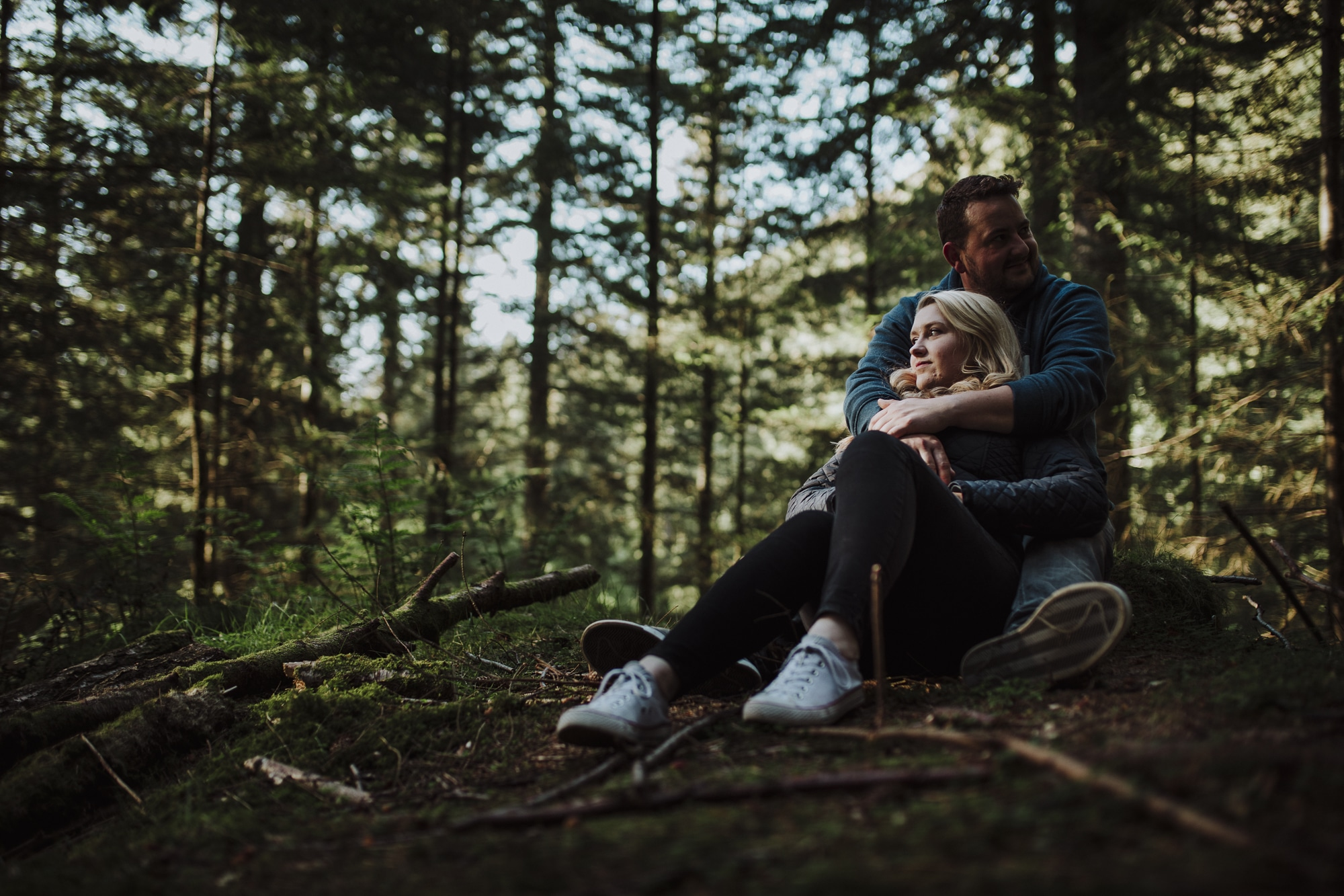 couple sitting down in love in the woods of dodds summit in the lake district