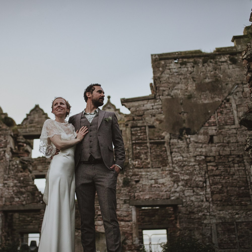 Beautiful couple standing on a wall at kirklinton Hall in cumbeia in a bohemian wedding