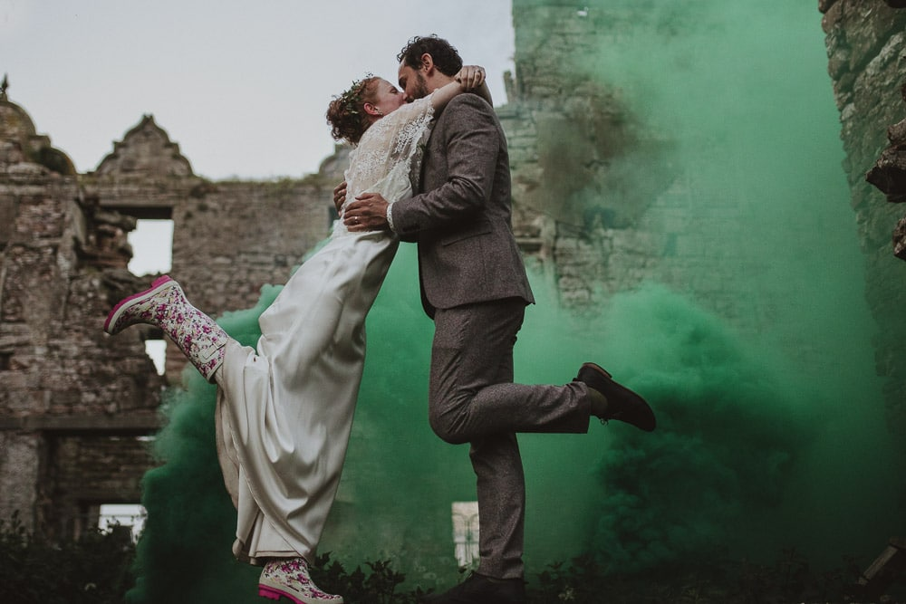 Bride and Groom standing on a wall at Kirklinton hall in cumbria with smoke grenades in the background