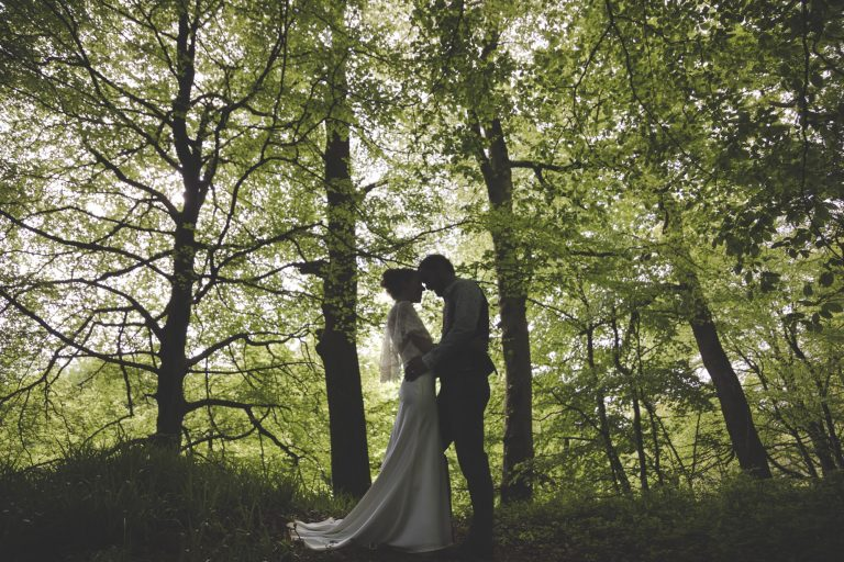 Bride and groom holding each other close in the grounds of Kirklinton Hall in the beautiful green woodlands
