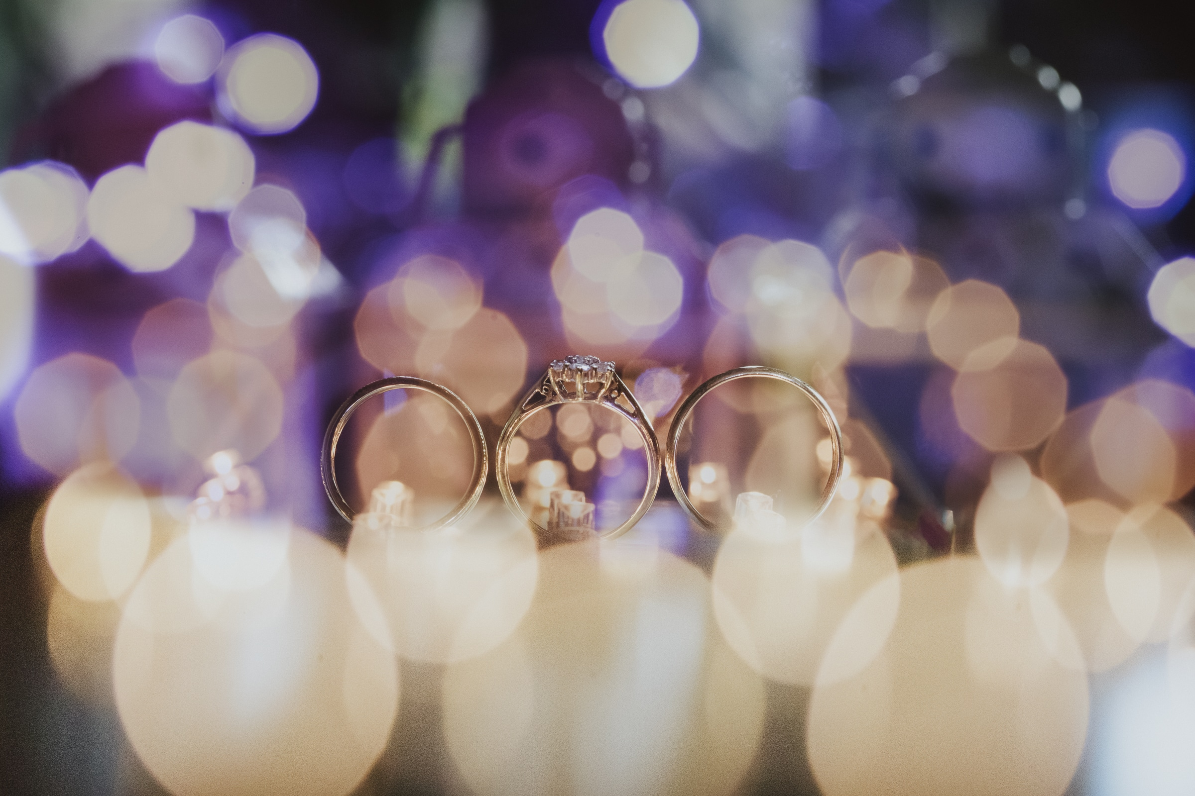 Kristina & Ashley Wedding Crow Nest Park Golf Club photograph of wedding rings with out of focus lights