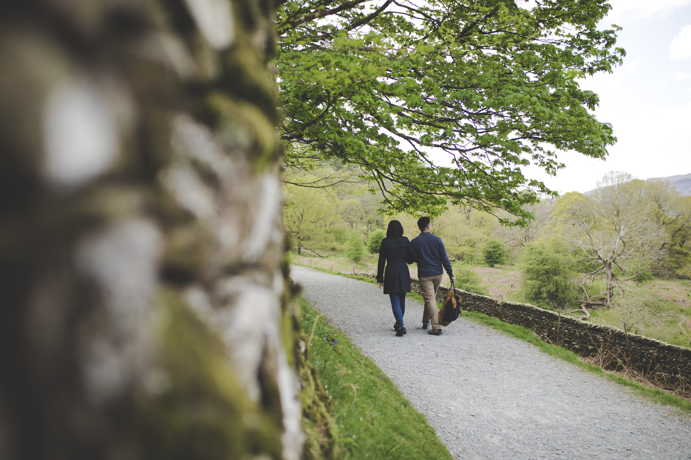 couple walking along foot path couples photoshoot on rydal water cumbria lake district wedding photographer