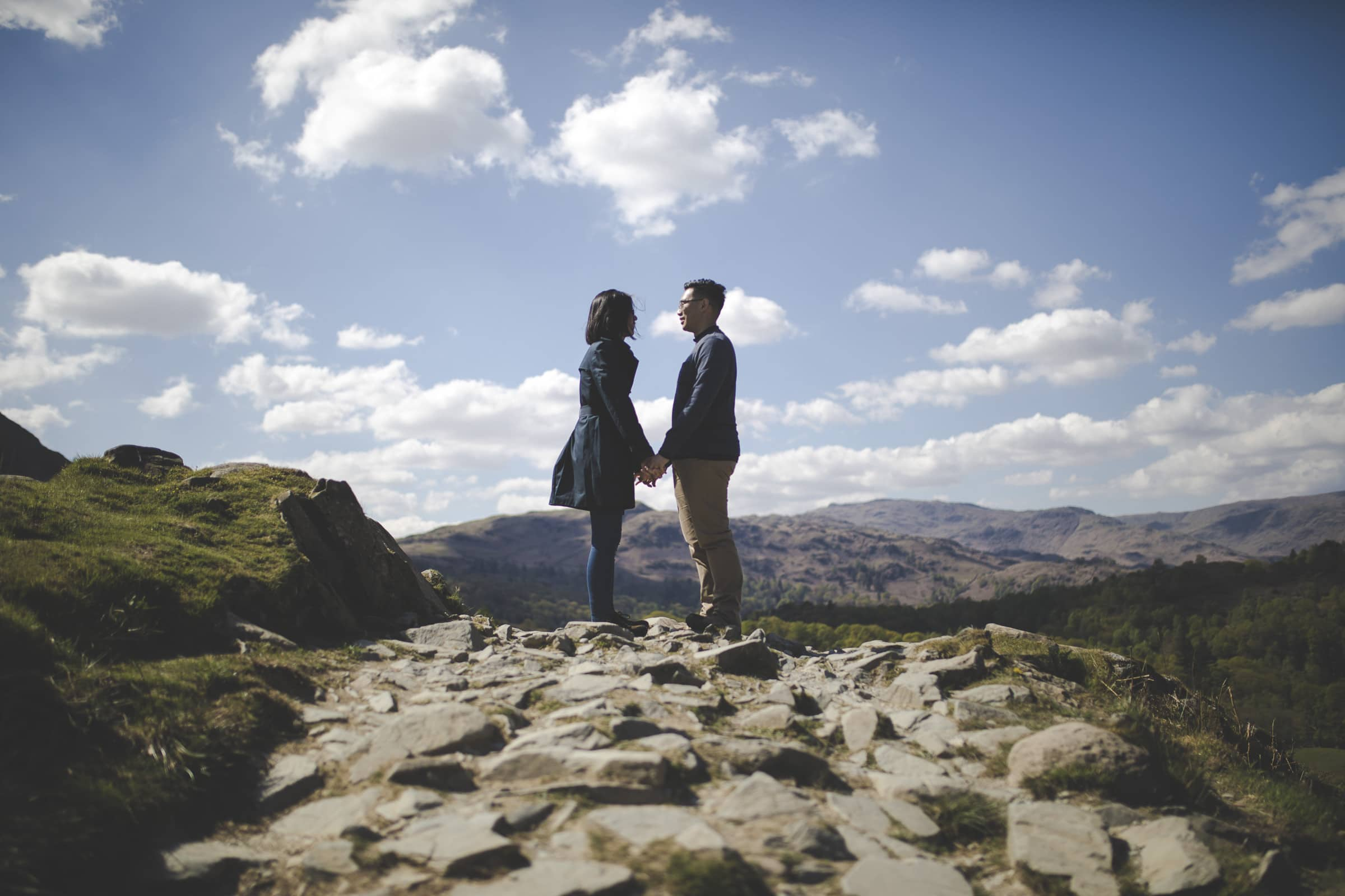 couple standing ontop of rydal caves in a couples photoshoot on rydal water cumbria lake district wedding photographer