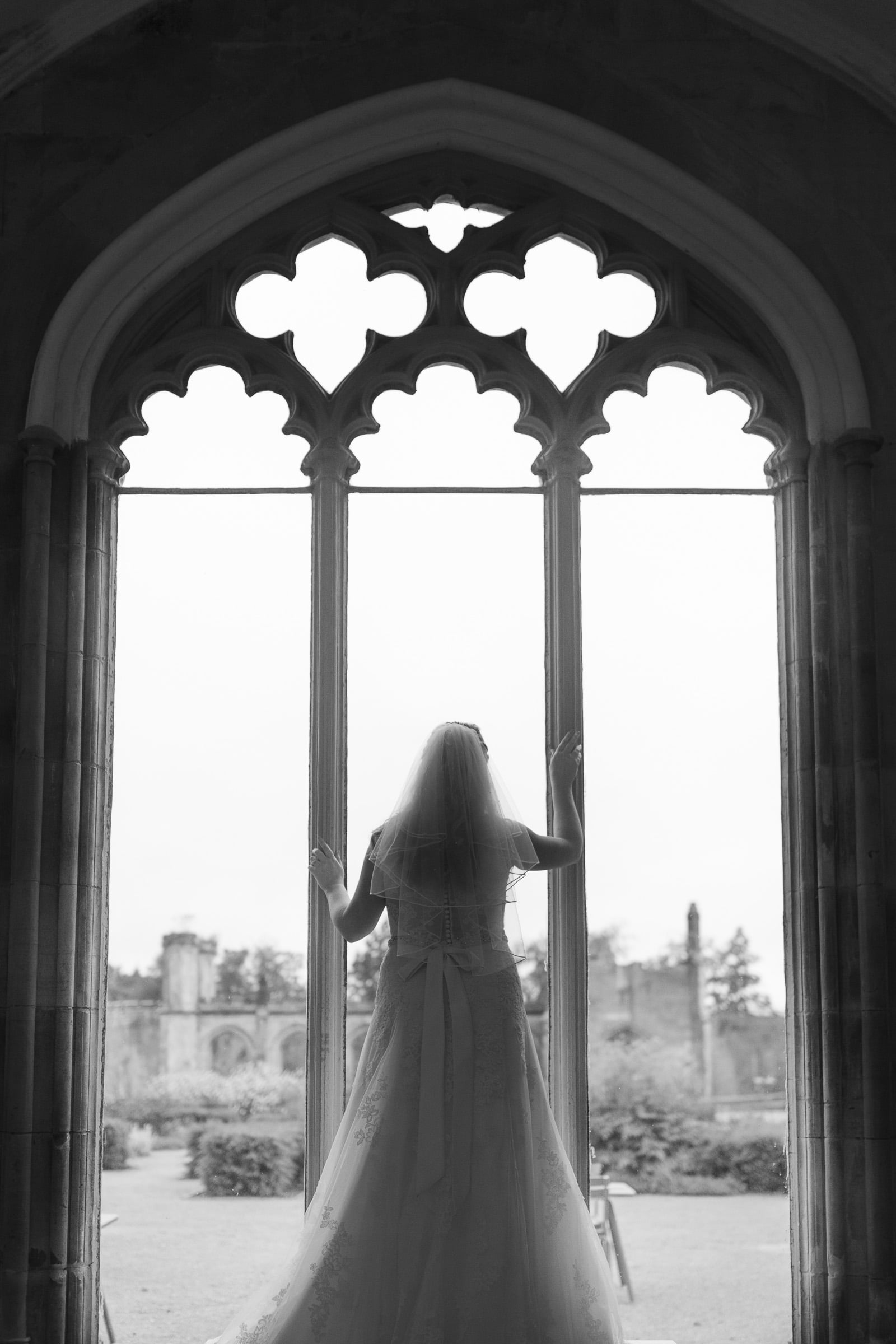 Becky Lowther Castle bridal photoshoot standing int he window of the castle
