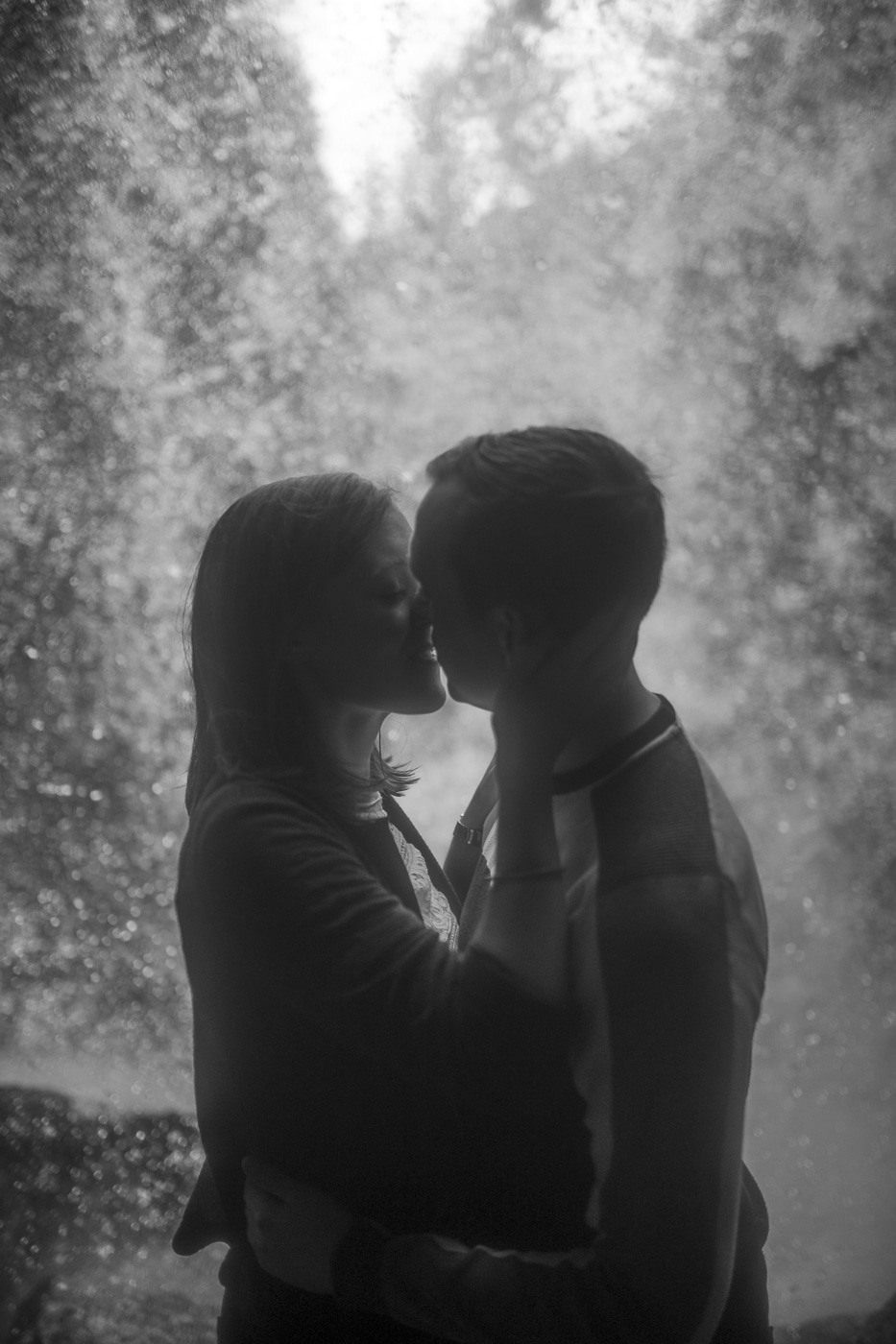 Couple standing in a hidden waterfall couple portrait session standing under the waterfall in couples shoot