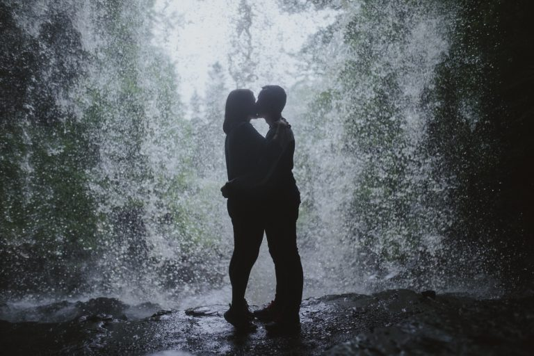 Couple standing in a hidden waterfall couple portrait session standing under the waterfall