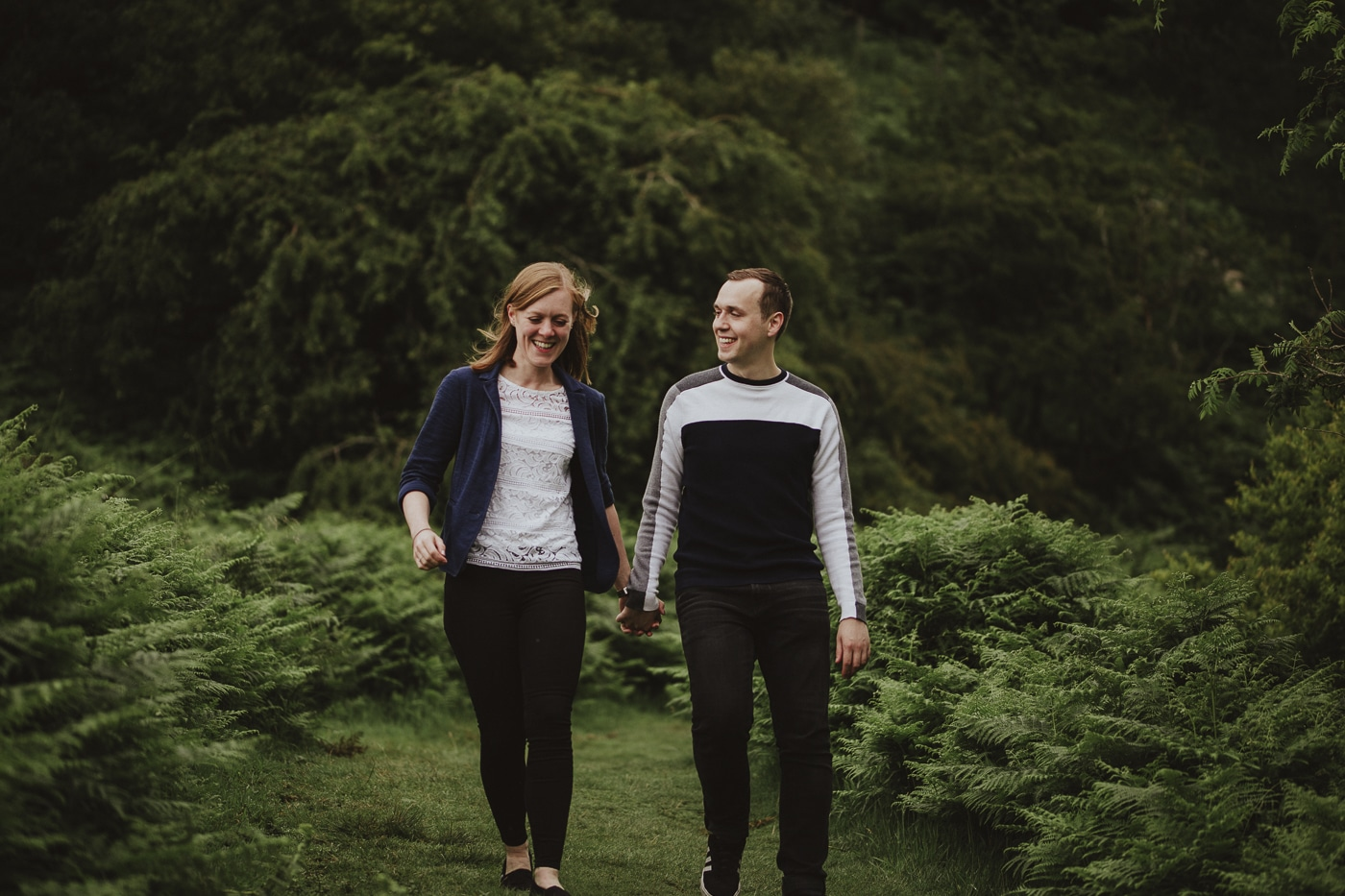 Couple walking down grassy path in Cumbria Portrait