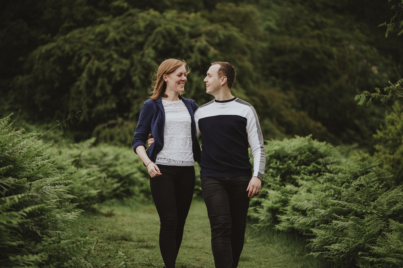 Couple laughing at each other walking down a path in Cumbria