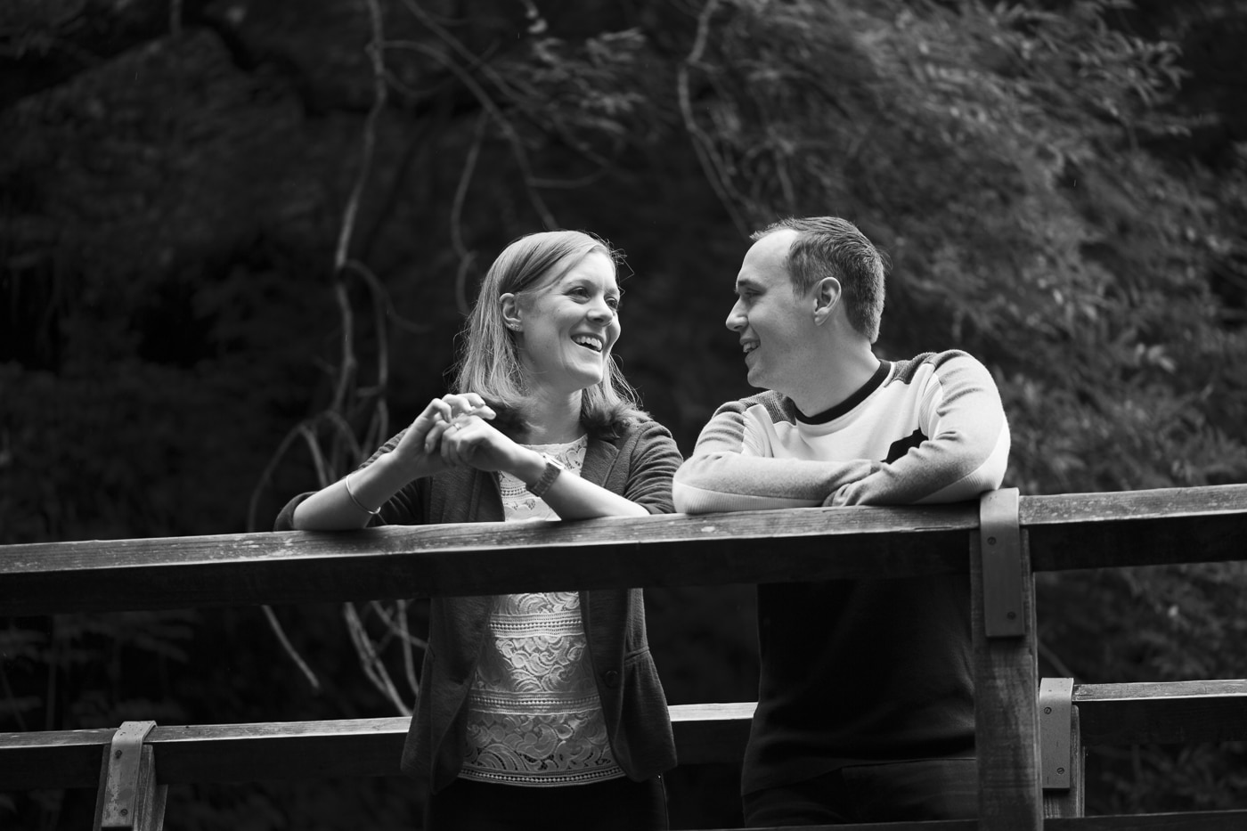 Couple standing on a bridge smiling at each other on a hidden waterfall photoshoot