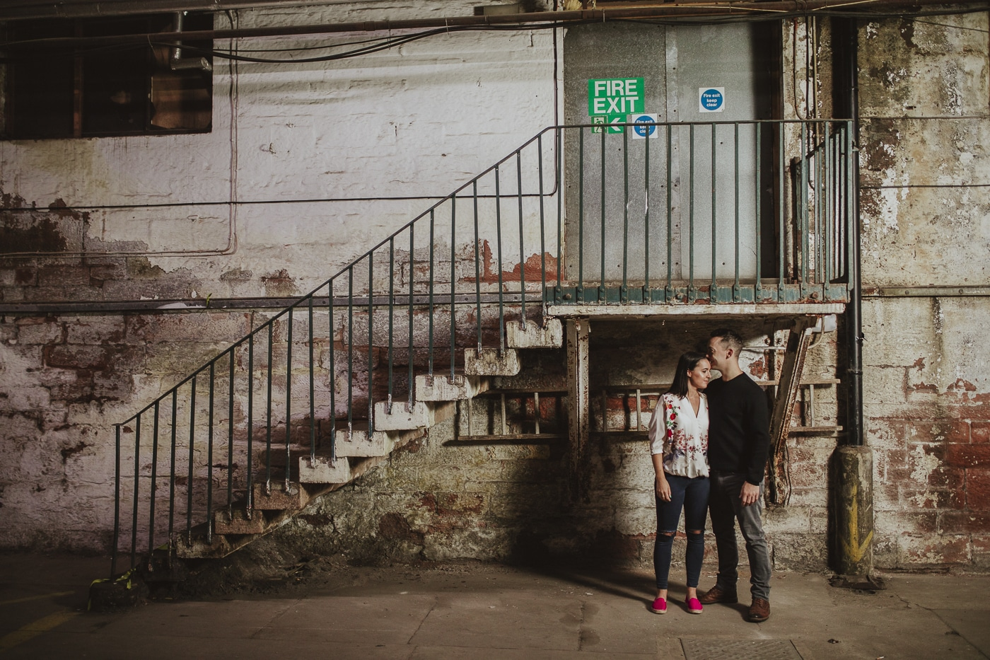 couple holding each other in an underground railway station Couples portrait session