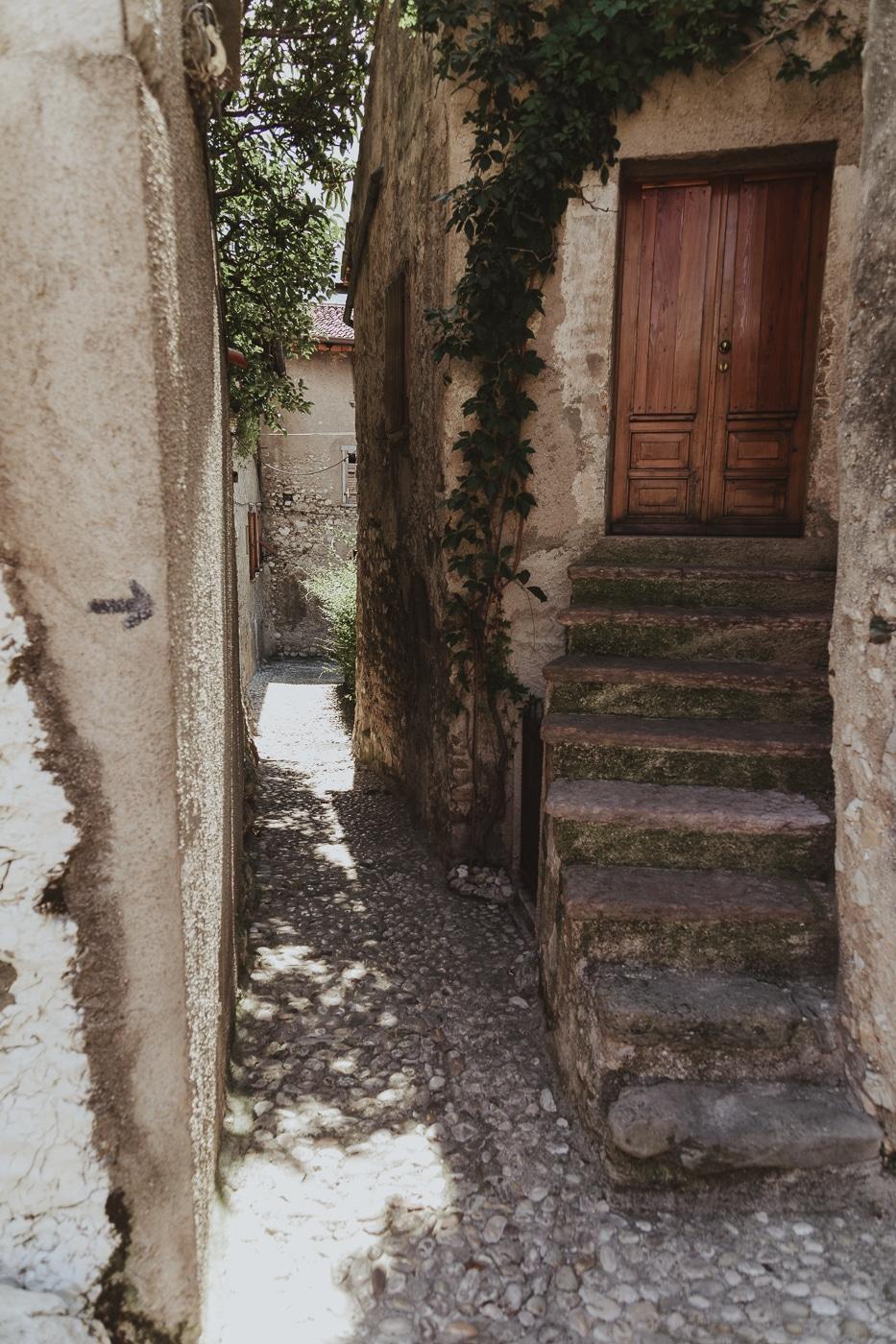 small passageway between buildings and stone steps to wooden door