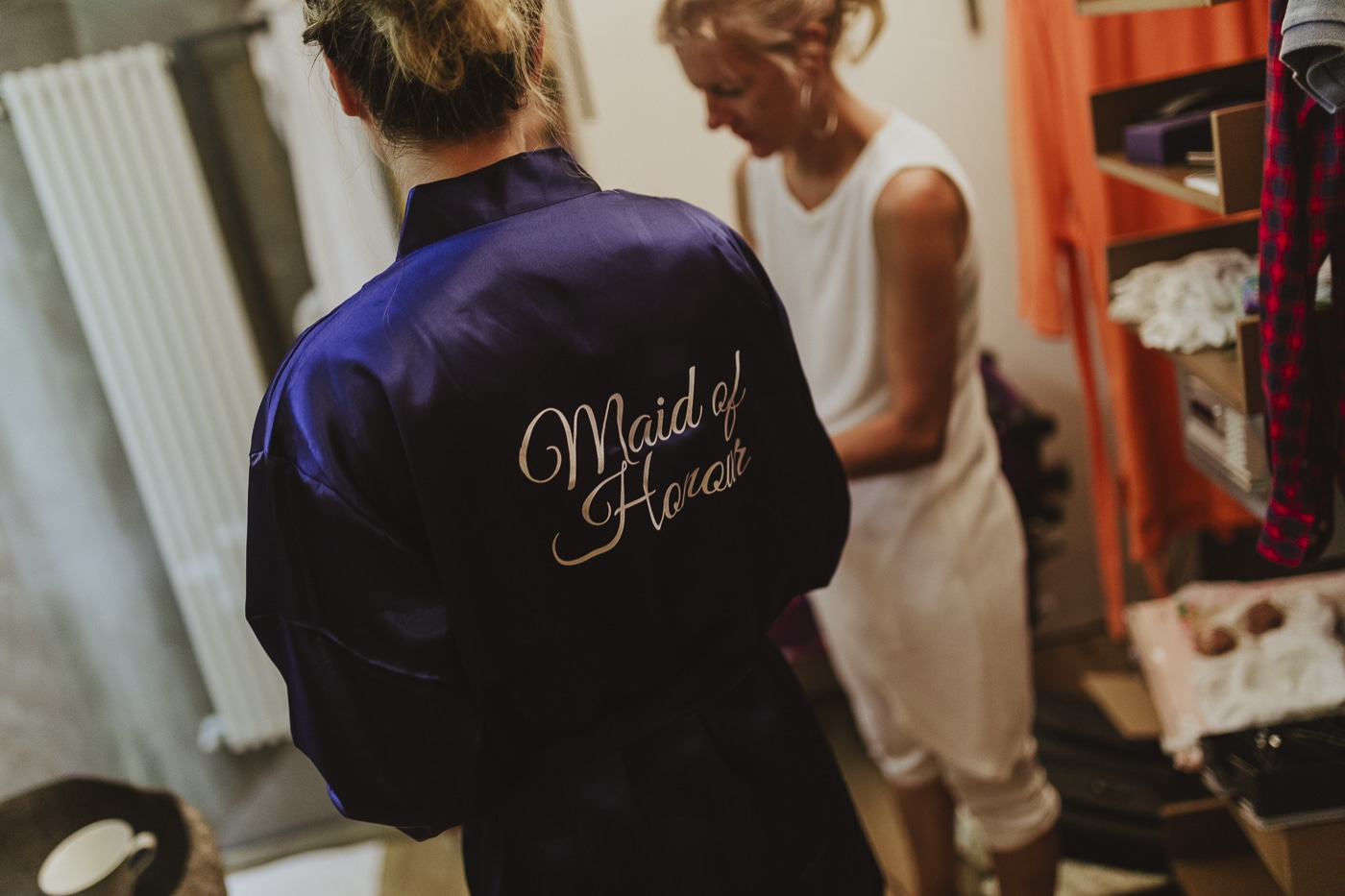 Maid of honour blue dressing gown with bride in background