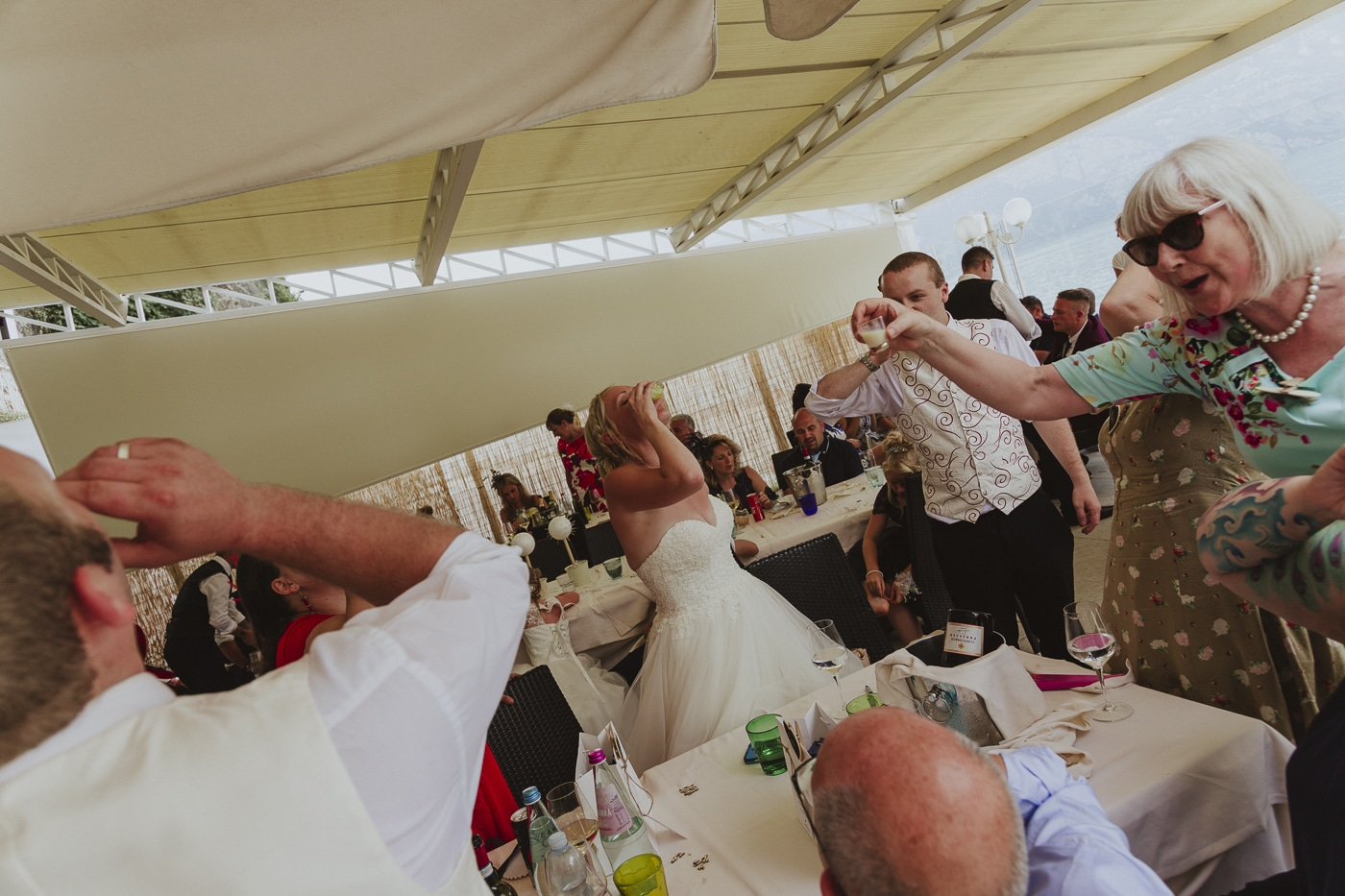 Bride, Groom and family drinking shots of alcohol amid their wedding reception by Joshua Wyborn