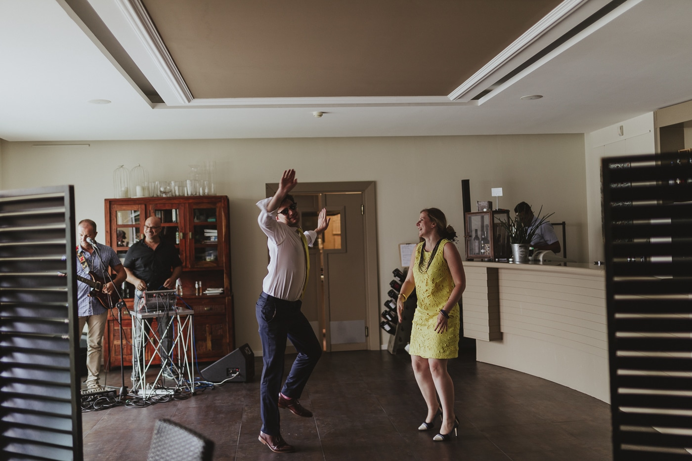 Dancing man in white shirt and woman in yellow dress with band in a bar by Joshua Wyborn