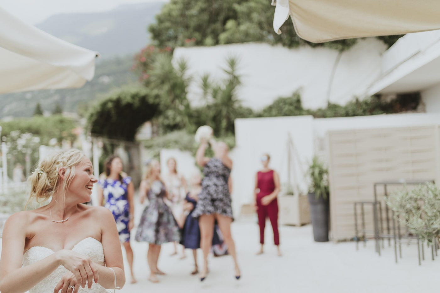 Happy bride throwing bouquet of white flowers to group of women who are jumping up to catch it by Joshua Wyborn