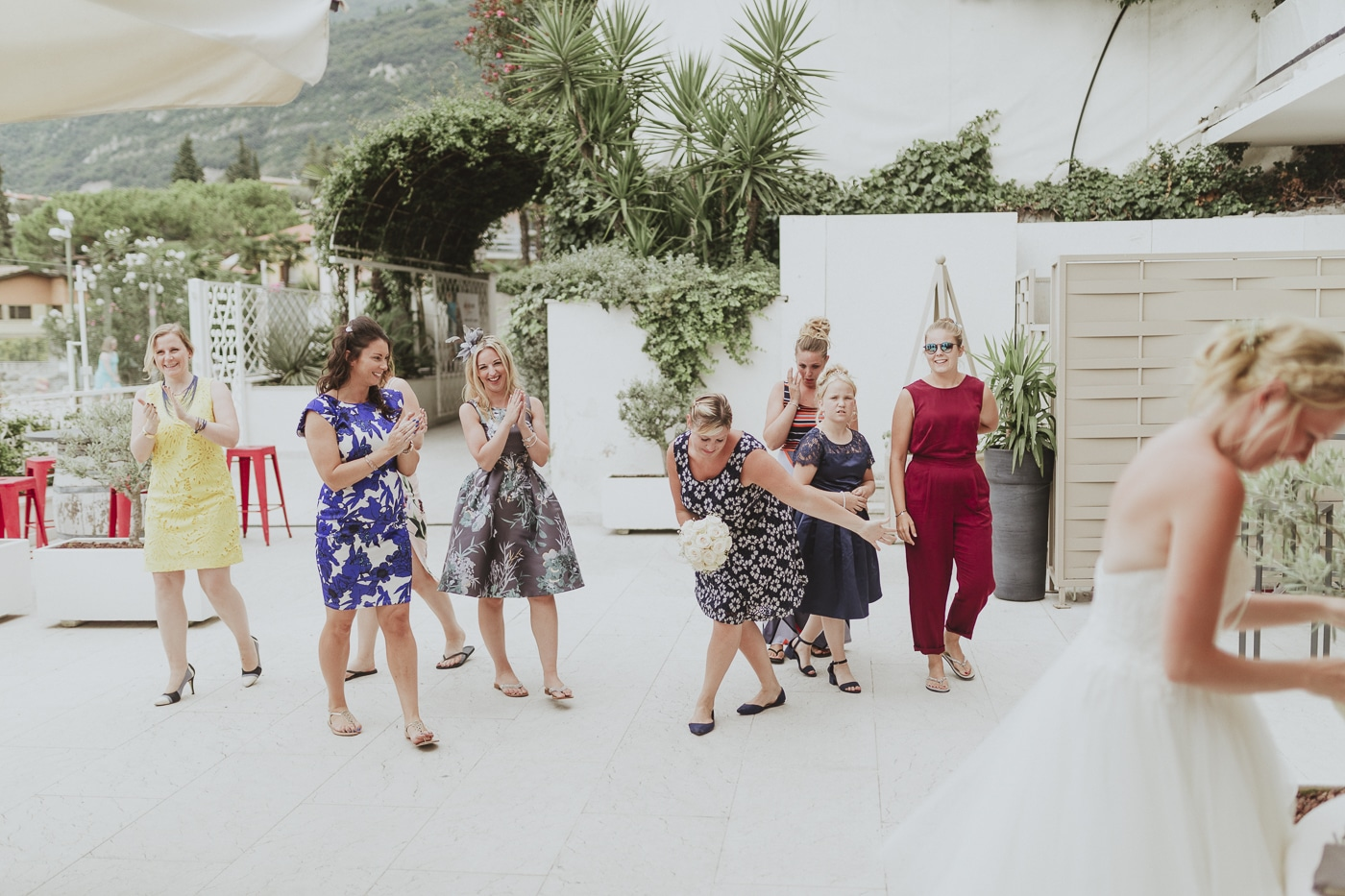 Group of women in wedding guest attire attempting to catch the bridal bouquet with white walkways and foliage in the background by Joshua Wyborn