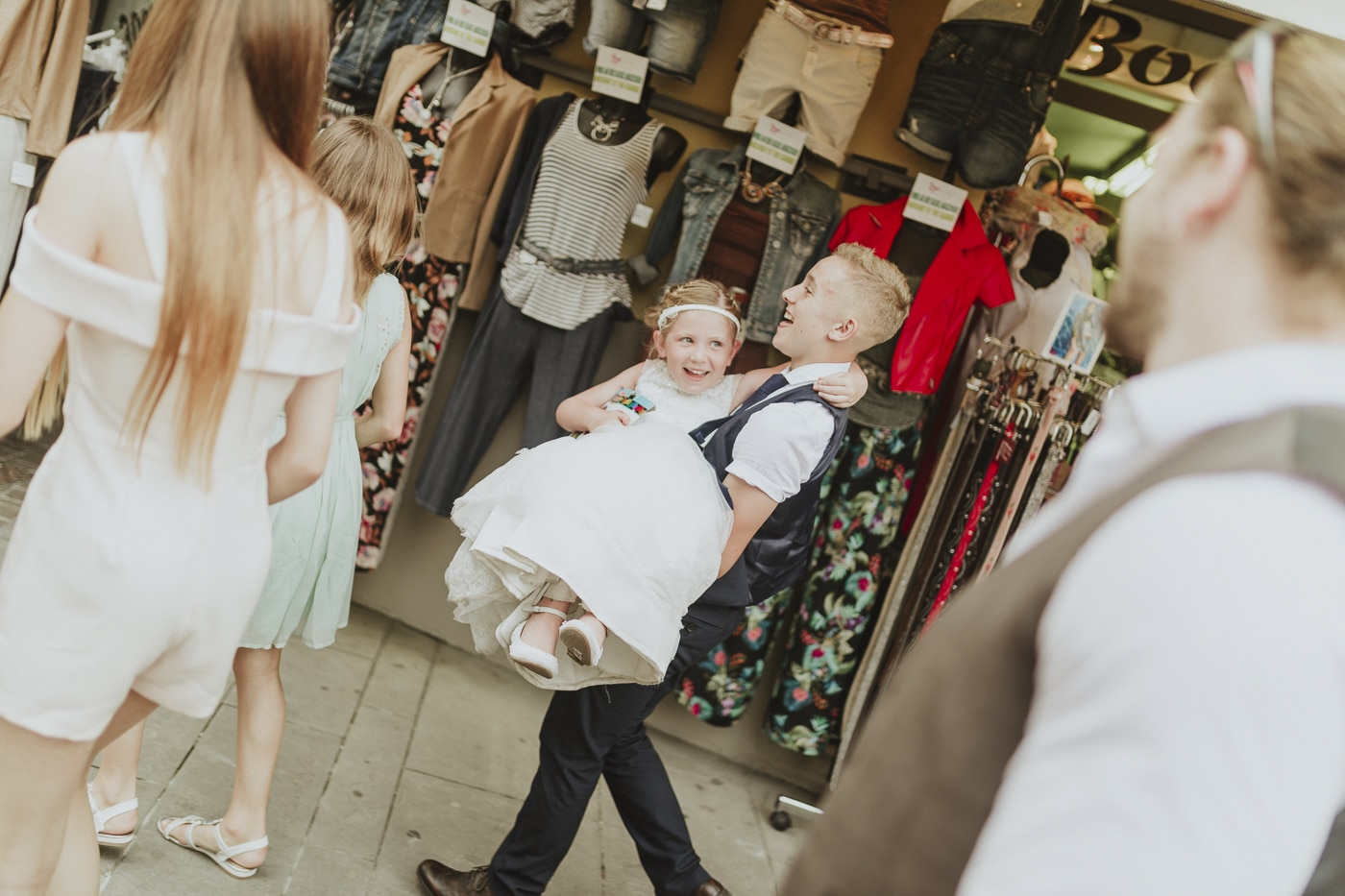 Young boy in white shirt and waistcoat carrying young bridesmaid through a local market in lake garda, italy by Joshua Wyborn