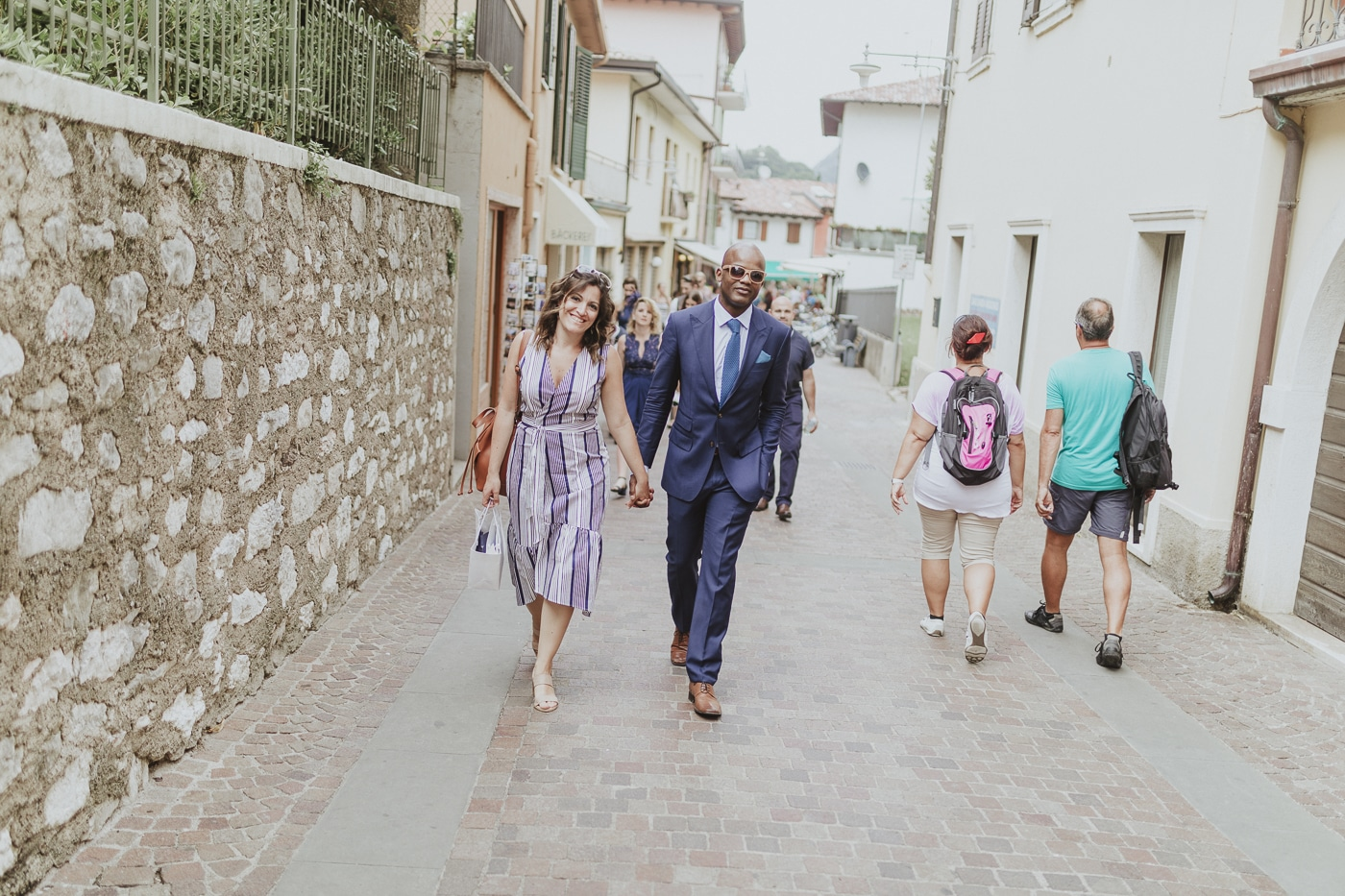 Woman in stripey dress and man in sunglasses and blue suit walking along a road in lake garda italy amongst other wedding guests and tourists alongside a traditonal stone wall by Joshua Wyborn