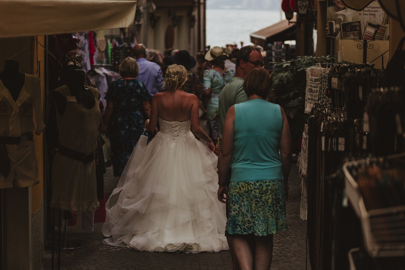Bride in wedding dress walking through a local market with crowds of tourists and the lake in the distance by Joshua Wyborn