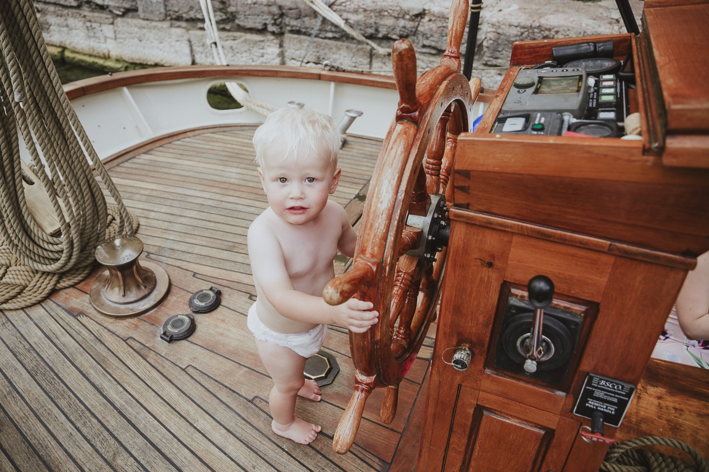 Small blond haired toddler steering a yacht using the steering wheel with ropes in the backgound by Joshua Wyborn