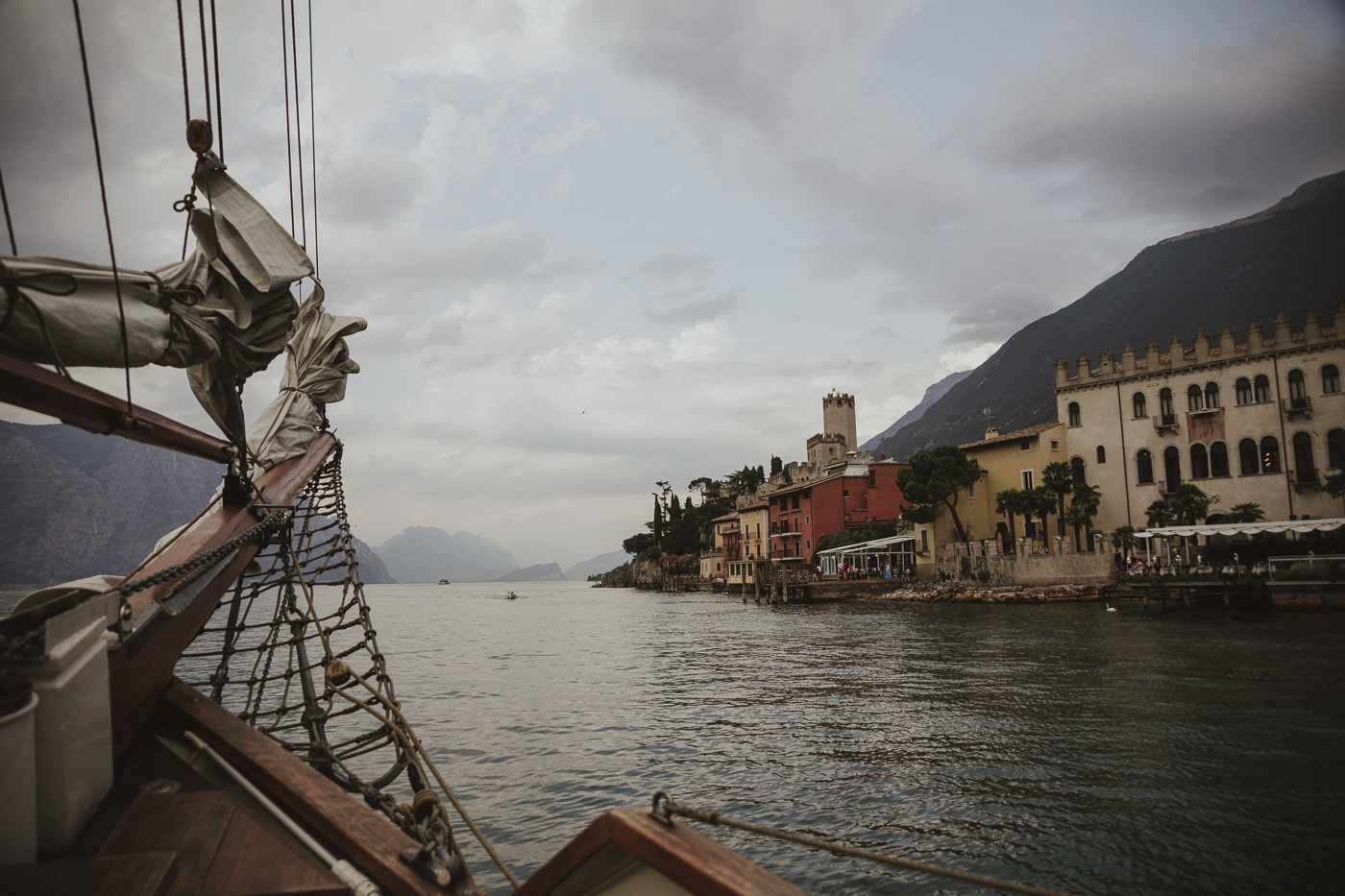 Mountains and traditional buildings seen from the edge of a yacht sailing on lake garda in italy by Joshua Wyborn