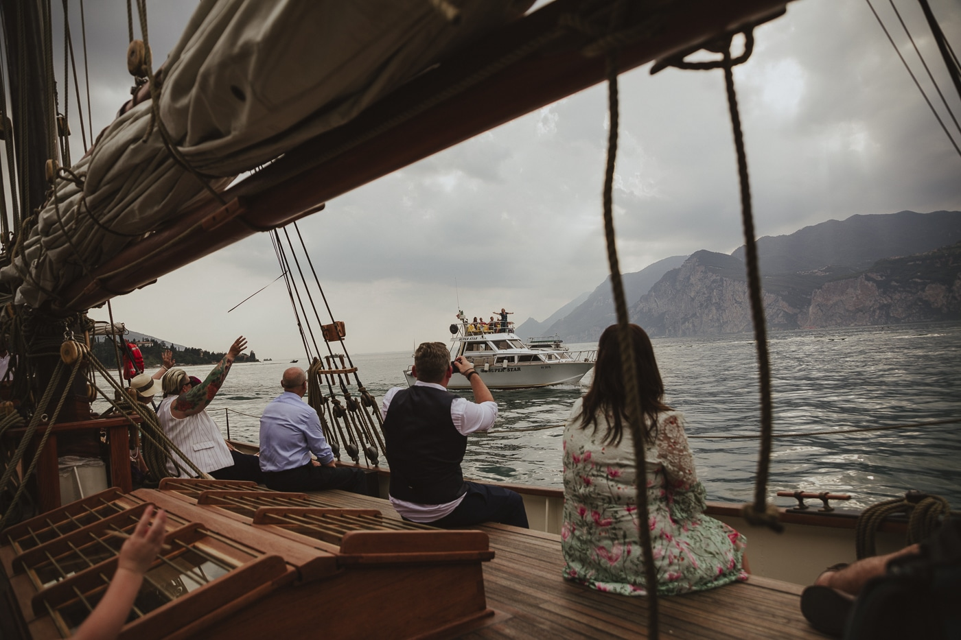 Wedding guests sitting aboard a yacht waving at another boat passing on lake garda in italy with mountains and cloudy skies in the background by Joshua Wyborn
