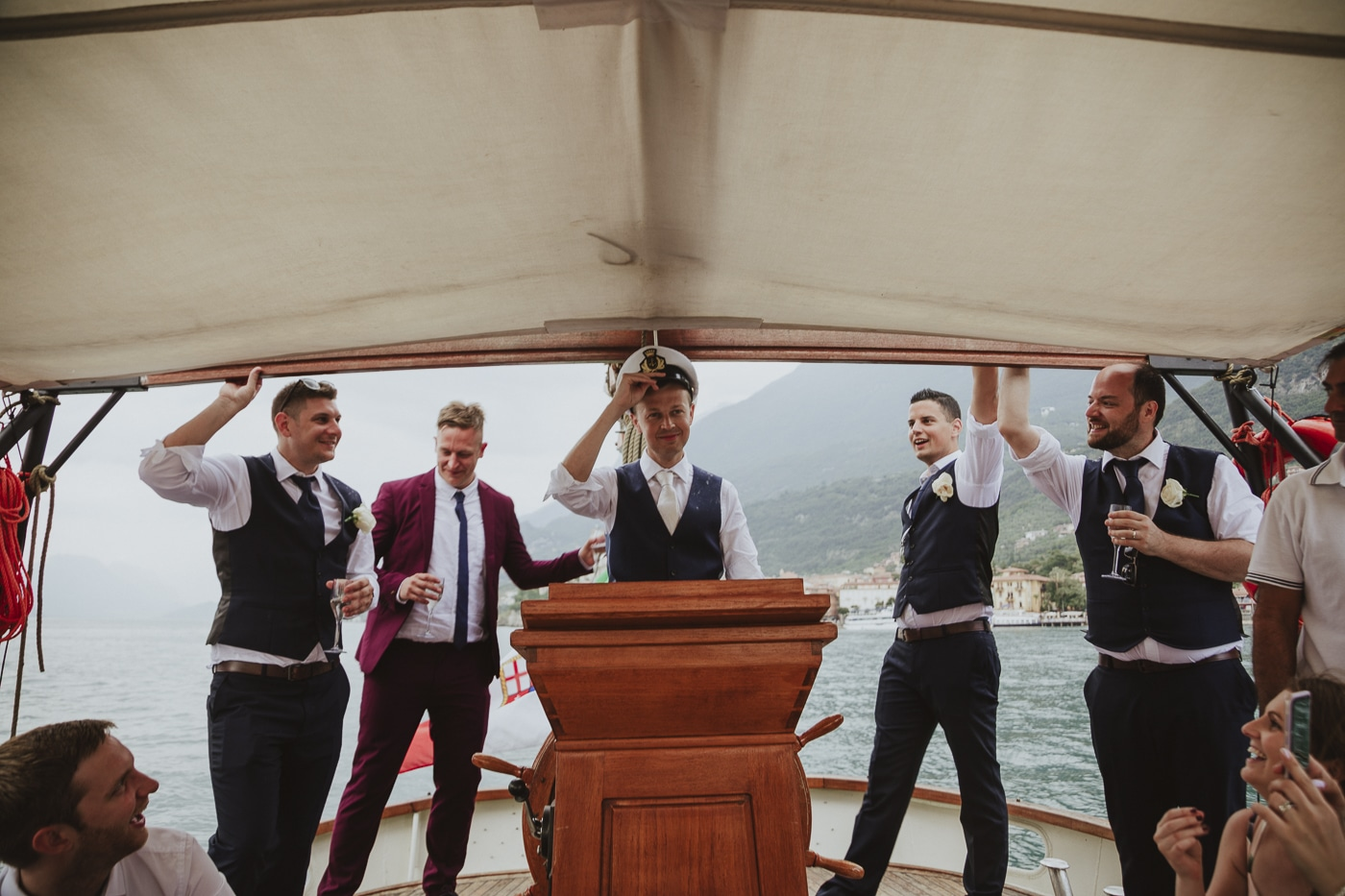 Groom in white shirt, tie and grey waistcoat wearing a captains hat aboard a yacht with his groomsmen on lake garda by Joshua Wyborn