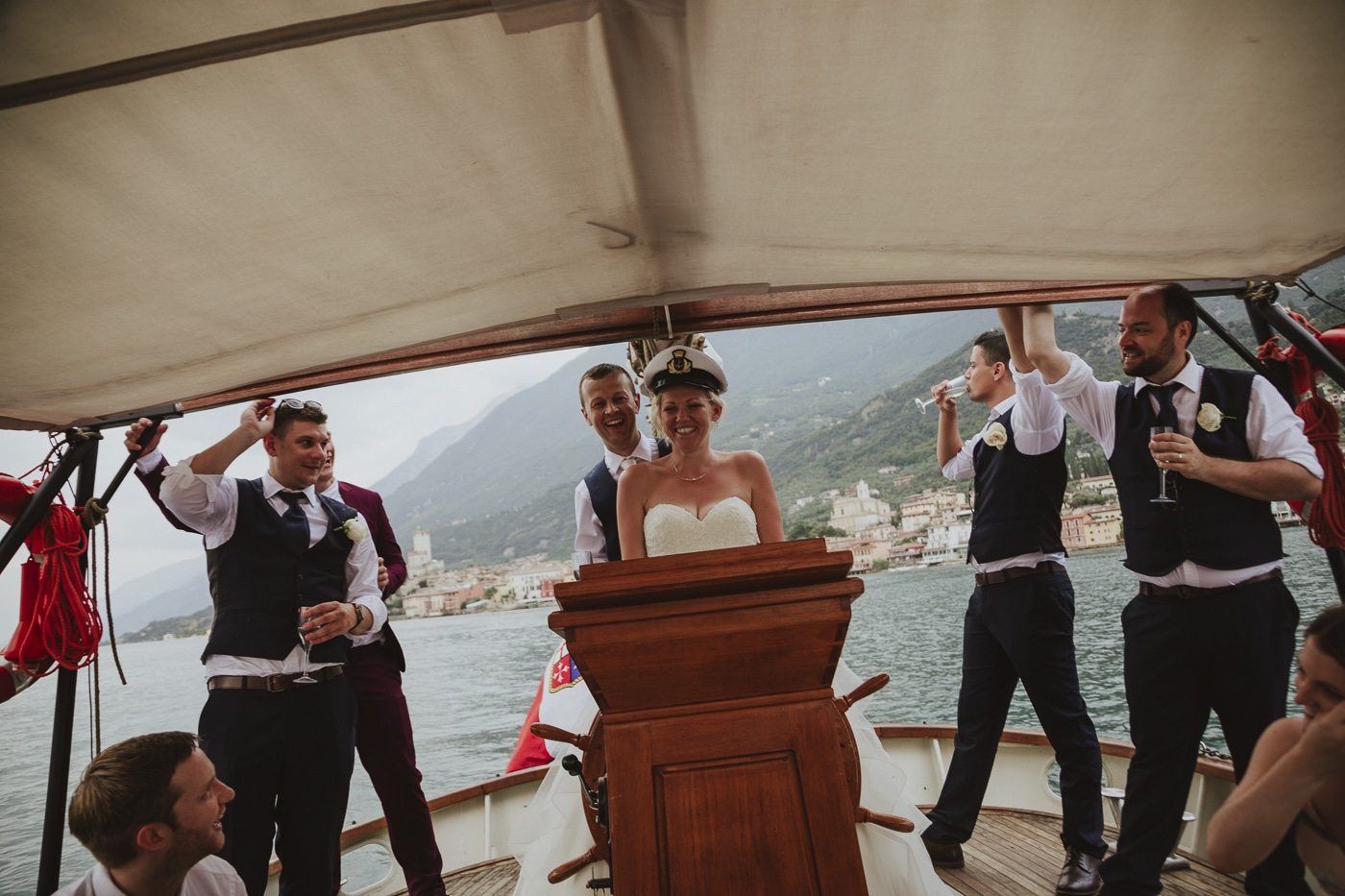 Bride in white wedding dress wearing captains hat with groom, best man and ushers in the background with wedding guests aboard a yacht floating on Lake Garda in Italy by Joshua Wyborn