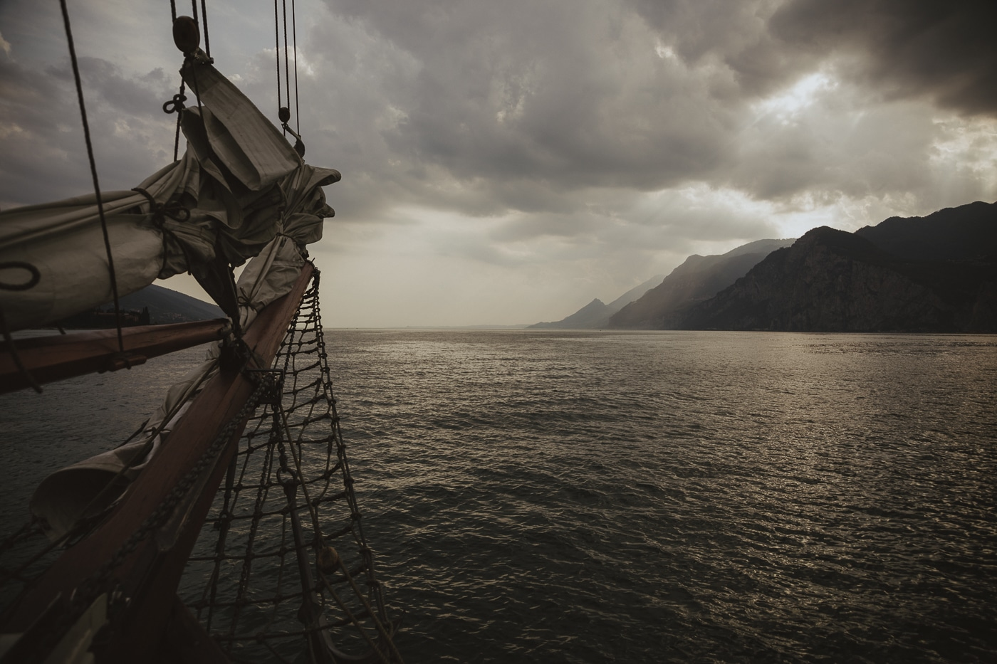 front of yacht with sails and a net, floating on lake garda in italy with dark moody clouds and mountains in the background by Joshua Wyborn