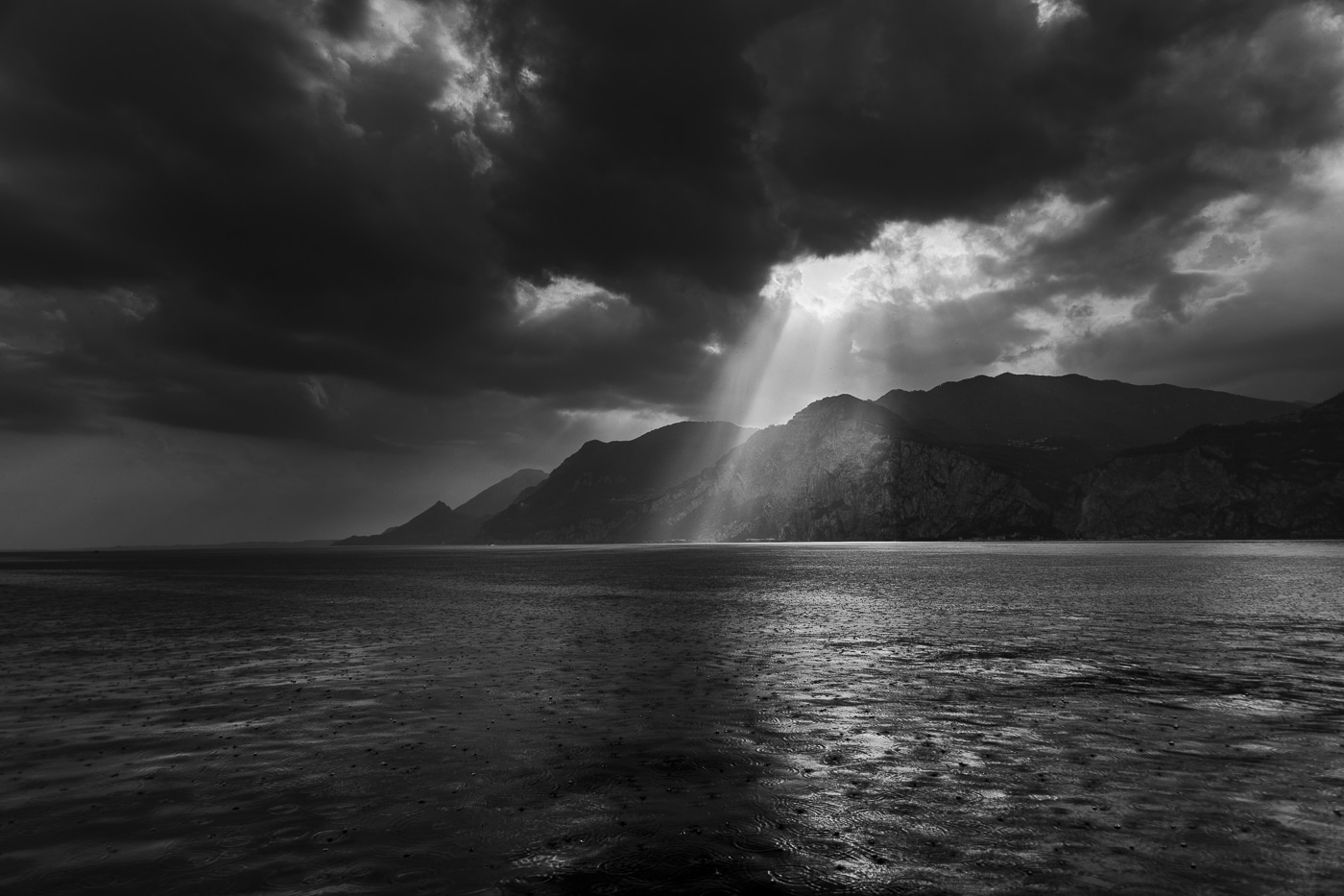 Sun rays breaking through the dark clouds and waves with raindrops on in front of mountains of lake garda in italy by Joshua Wyborn