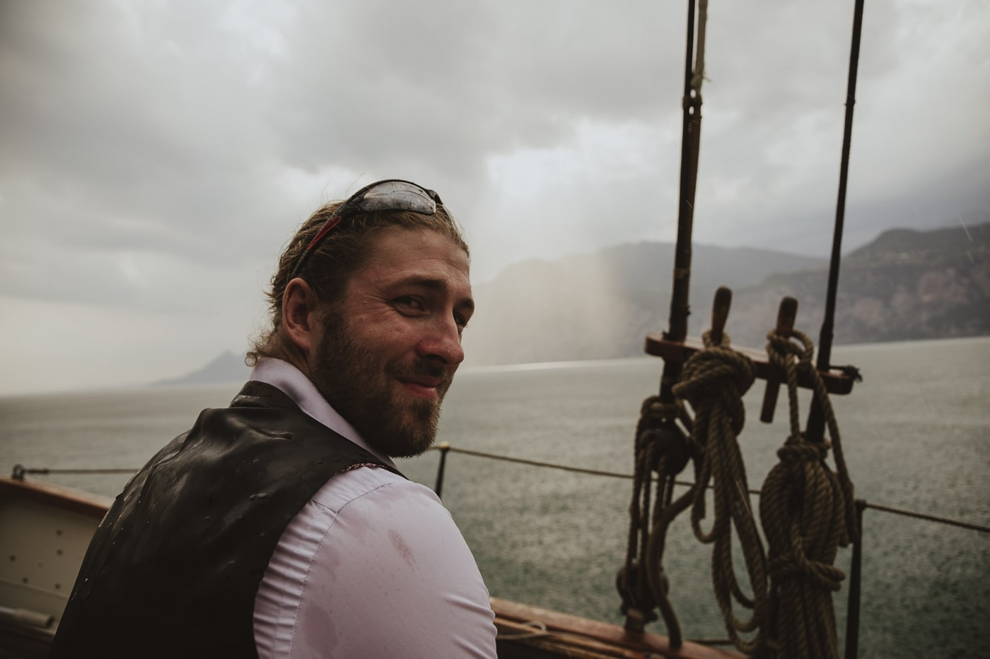 bearded man with sunglasses and a waistcoat in wedding atire sitting aboard a yacht on lake garda italy with ropes and mountains in the background by Joshua Wyborn