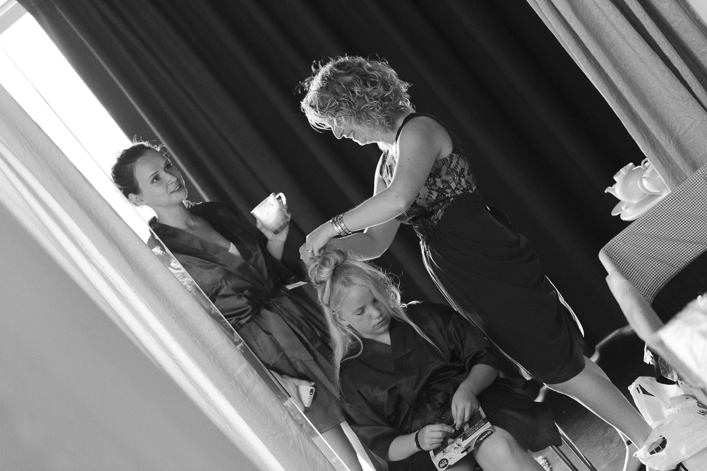 Bridesmaid having hair done while woman talk behind her