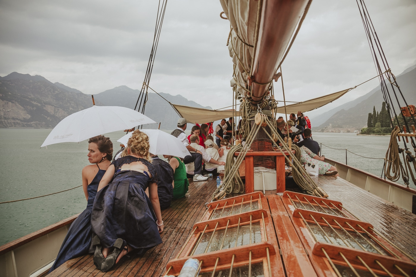 Wedding guests in dresses and suits sheltering under white umbrellas on a yacht in the rain with the mountains and lake garda in the background by Joshua Wyborn