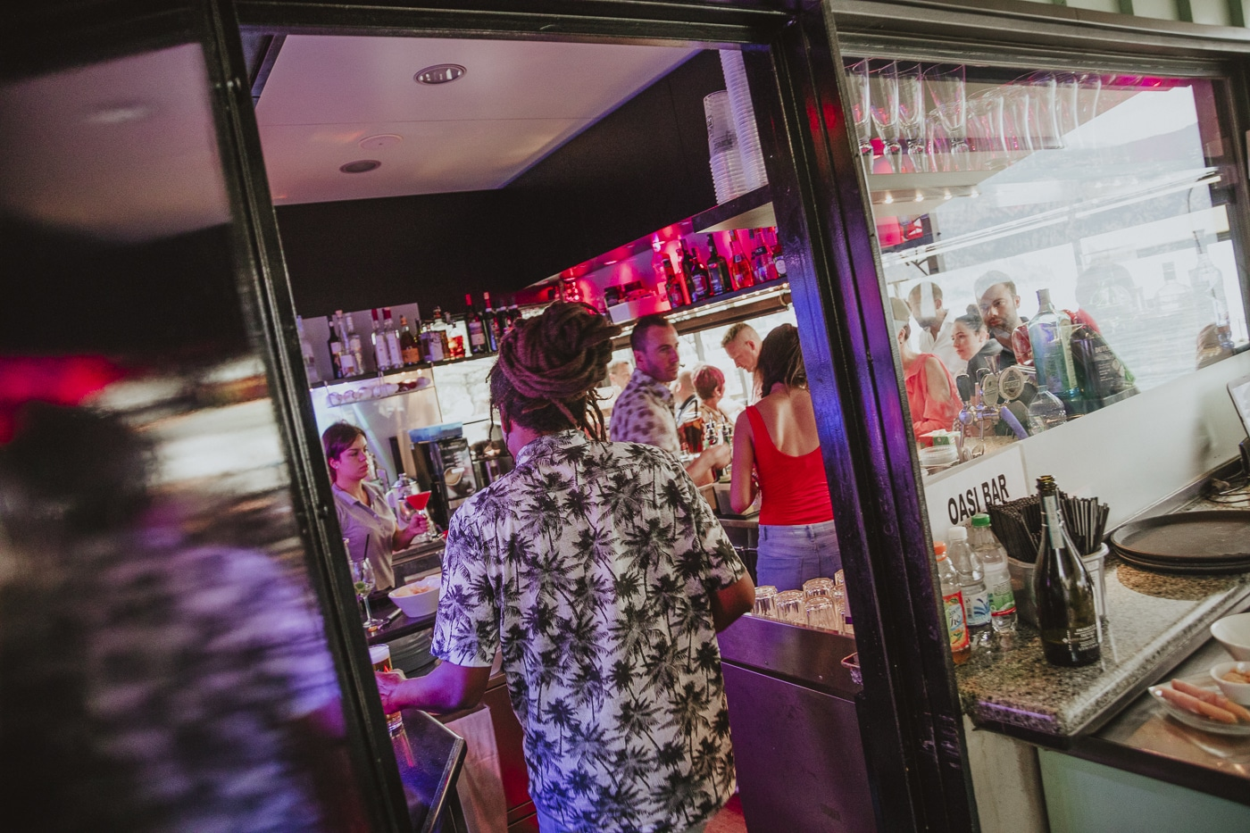 dreadlock man with tropical shirt working behind bar making drinks for a wedding in lake garda, italy by Joshua Wyborn