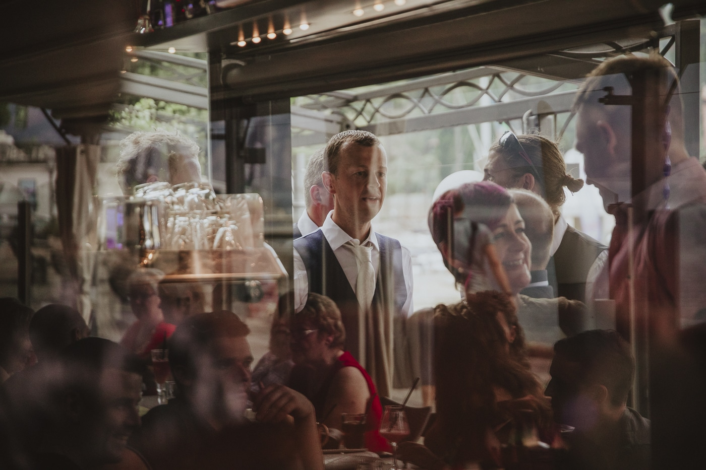 Reflection of glasses and wedding guests in suits for a wedding on lake garda italy