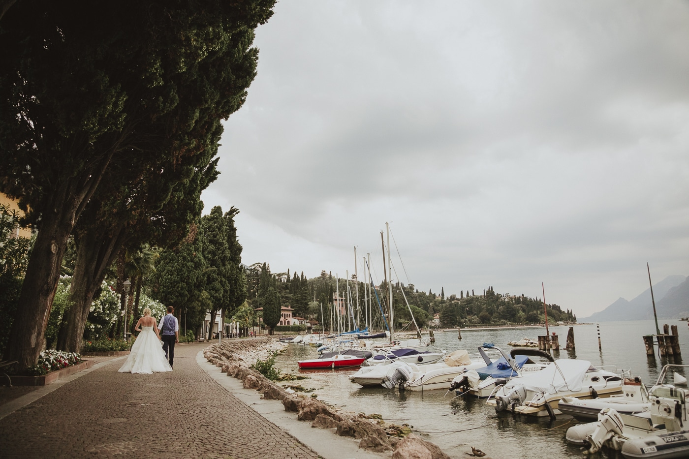 Bride and Groom walking along tree lined pathway next to a marina of boats in Lake Garda Italy with mountains in the background