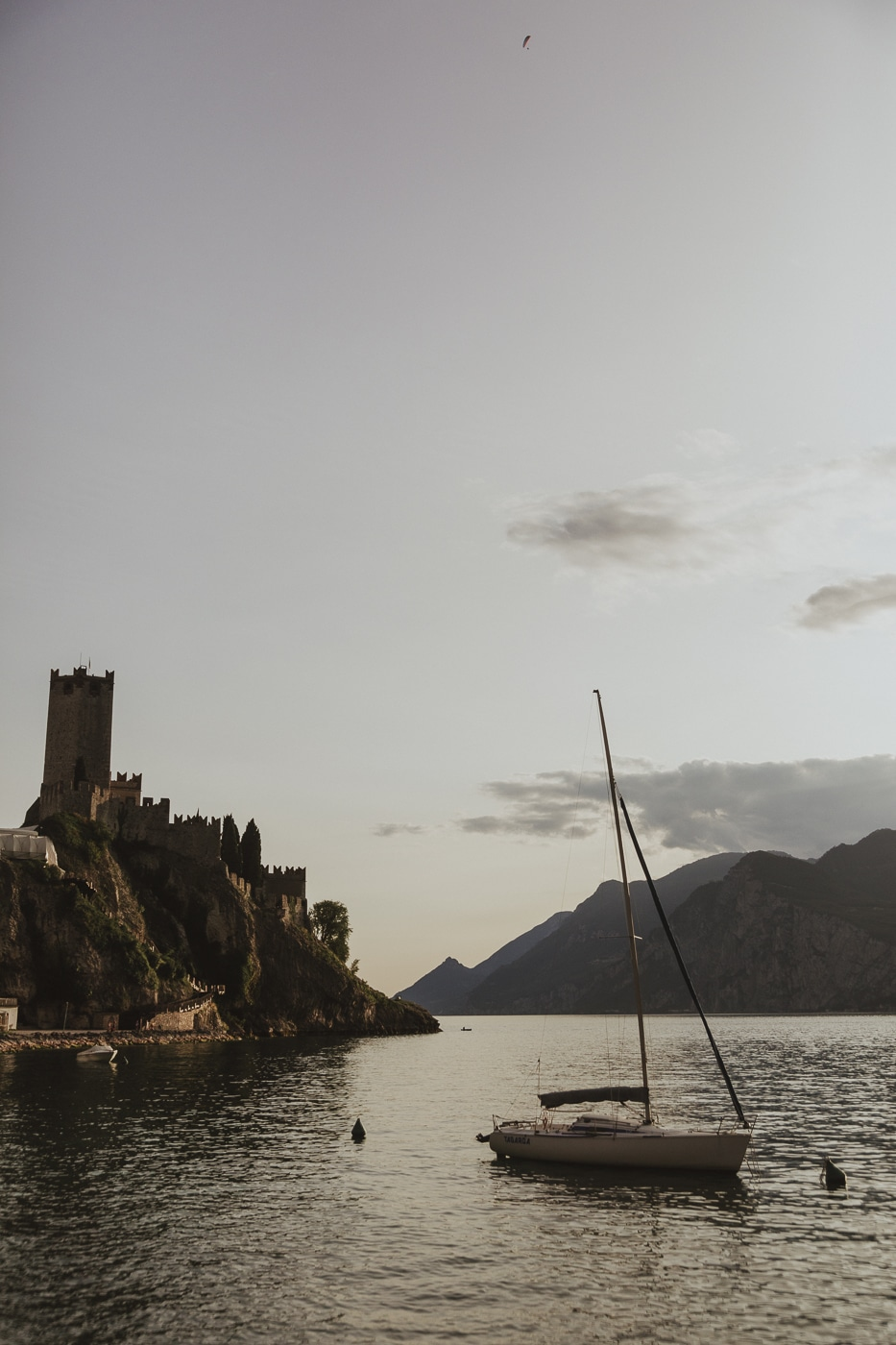 Castle on a cliff and floating white yacht on Lake Garda in Italy with mountains in the background and a grey cloudy sky