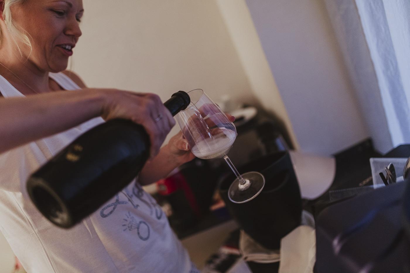 Bride pouring bubbles into a wine glass