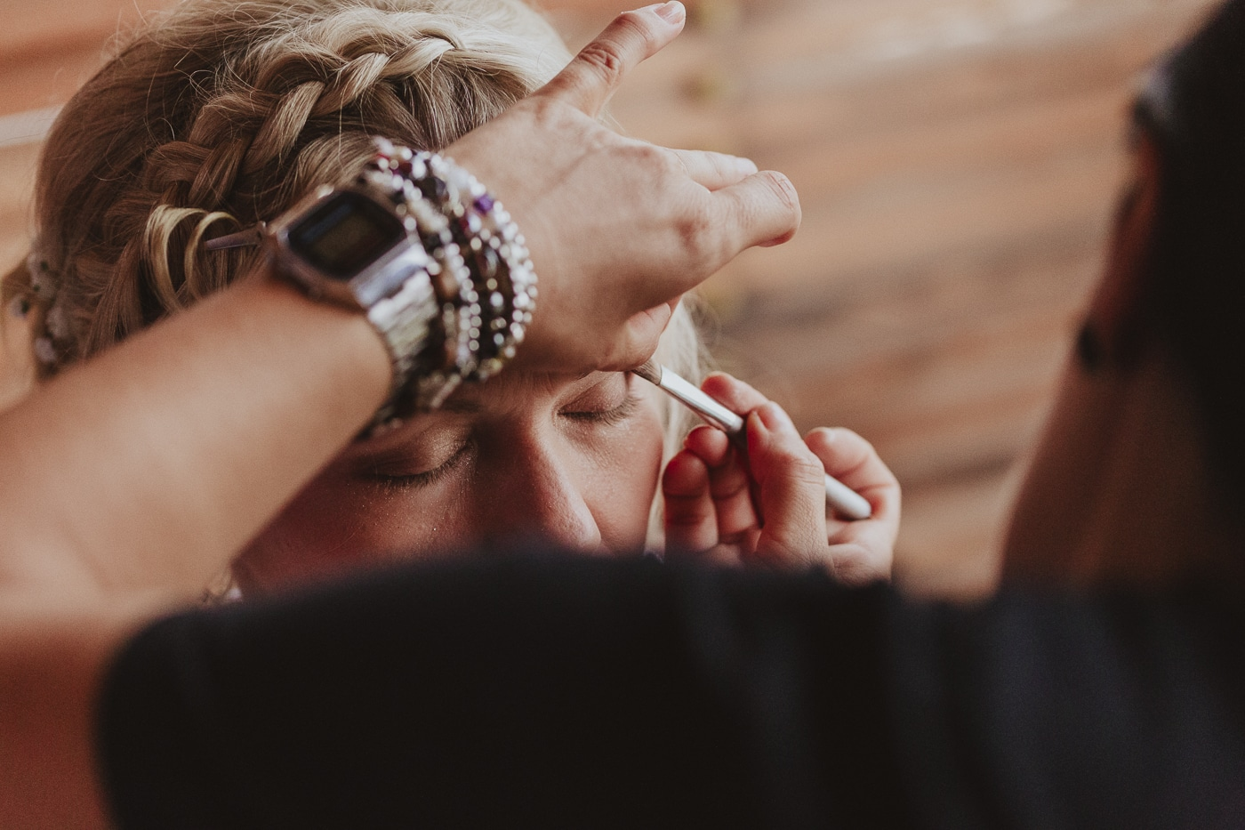 Bride getting makeup done by woman with bracelets and watch on wrist