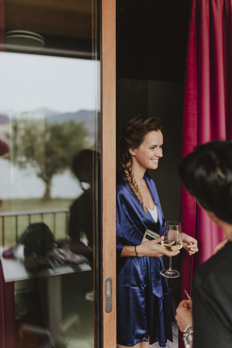 Bridesmaid walking through door wearing blue robe and carrying glass of wine