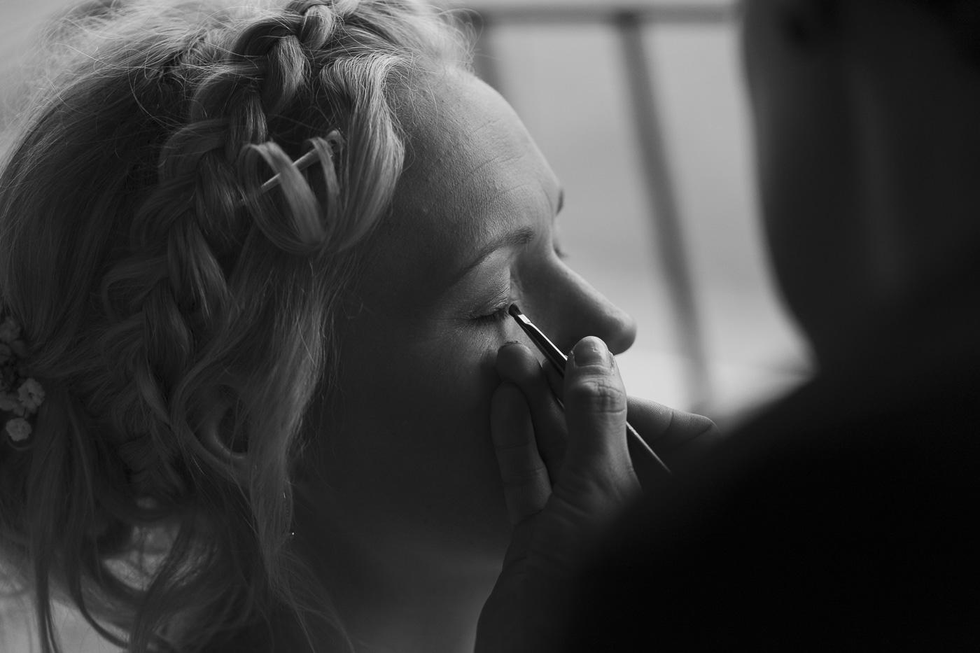 Bride with braid in hair gets eye makeup done