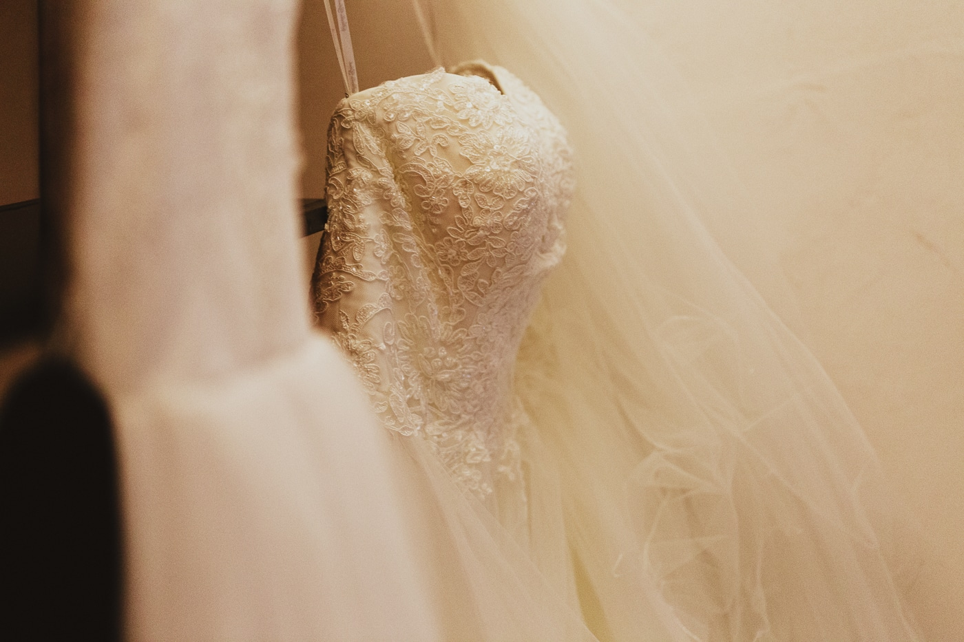 White beaded wedding dress hanging up