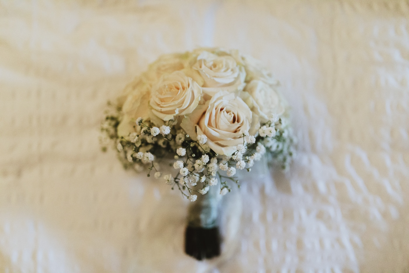 white roses with small white flowers surrounding in bouquet